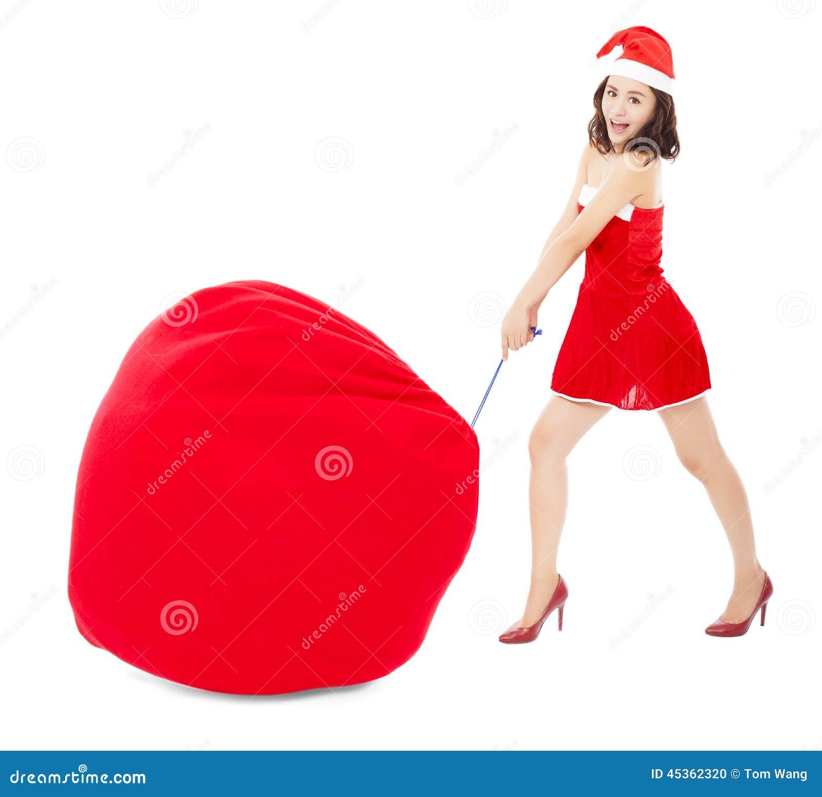 Jeune traction femelle un sac lourd de cadeau avec le costume de Noël