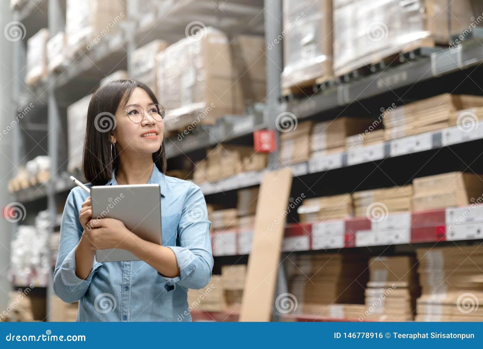 Jeune travailleur asiatique attirant, propriétaire, femme d entrepreneur tenant la tablette intelligente regardant le côté au-des