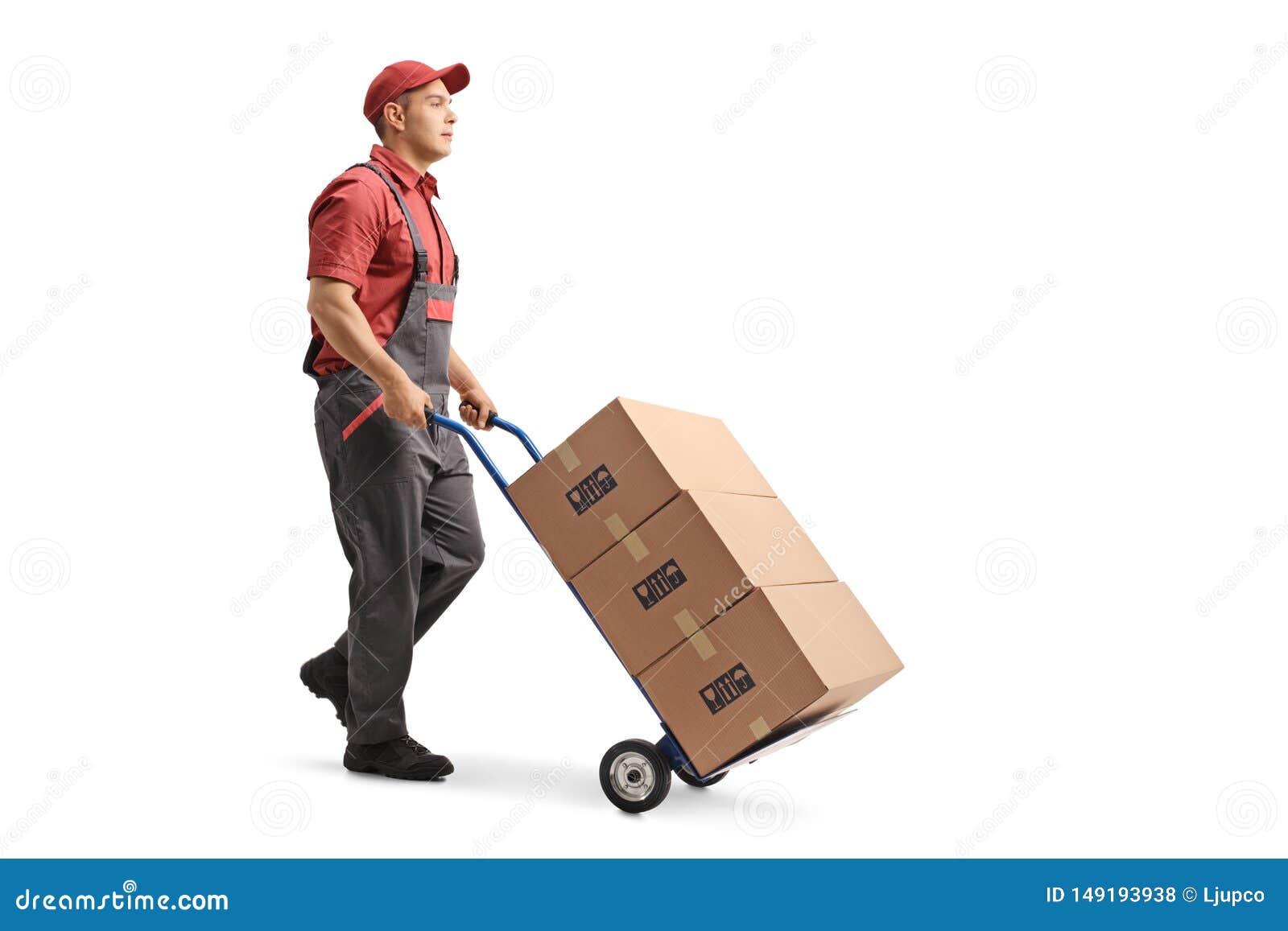 Jeune travailleur de sexe masculin dans un uniforme poussant des bo?tes sur un camion de main