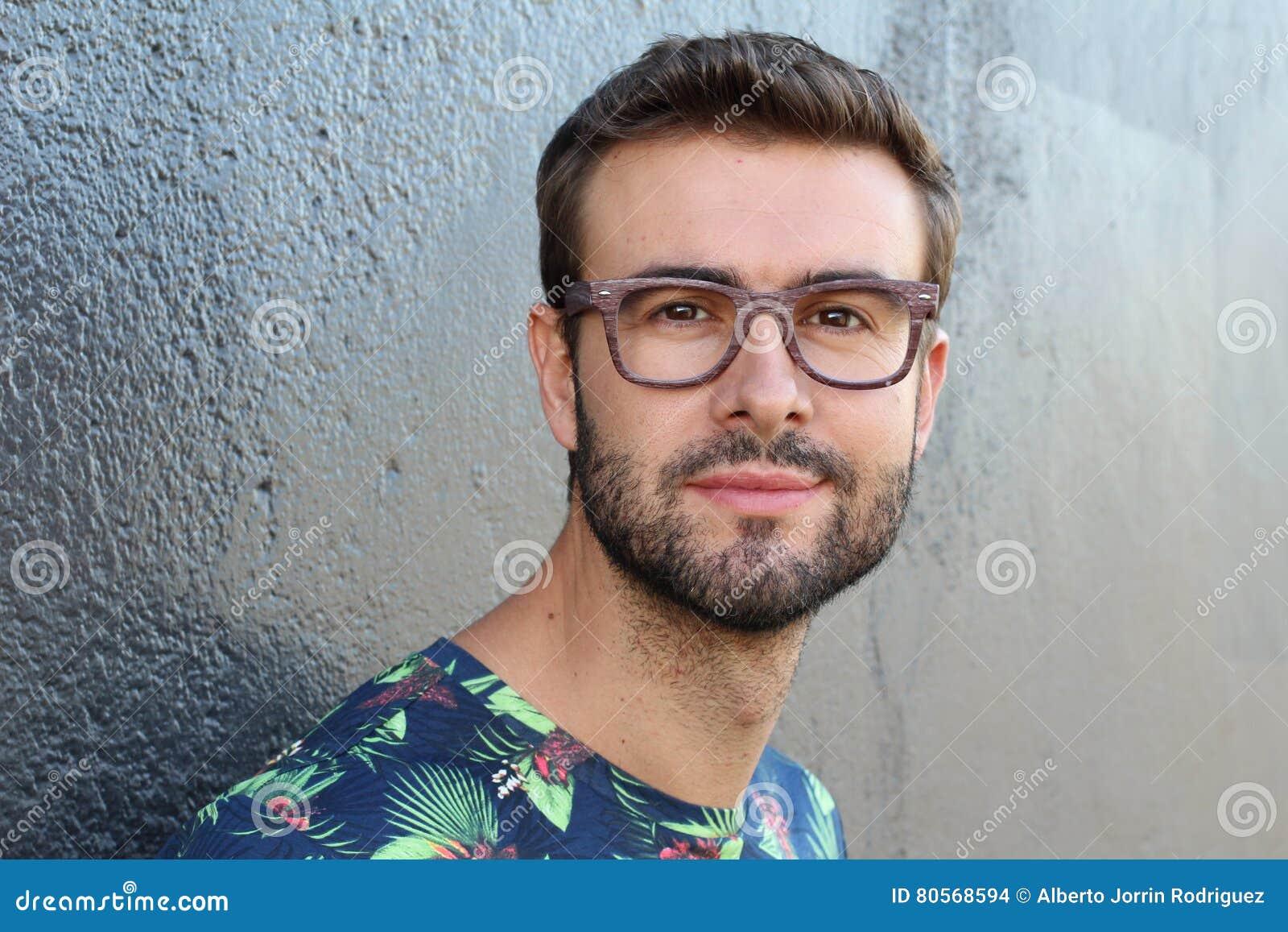Jeune type avec une barbe et moustache avec des verres dans une chemise fleurie ou florale posant sur la rue, homme de mode, styl