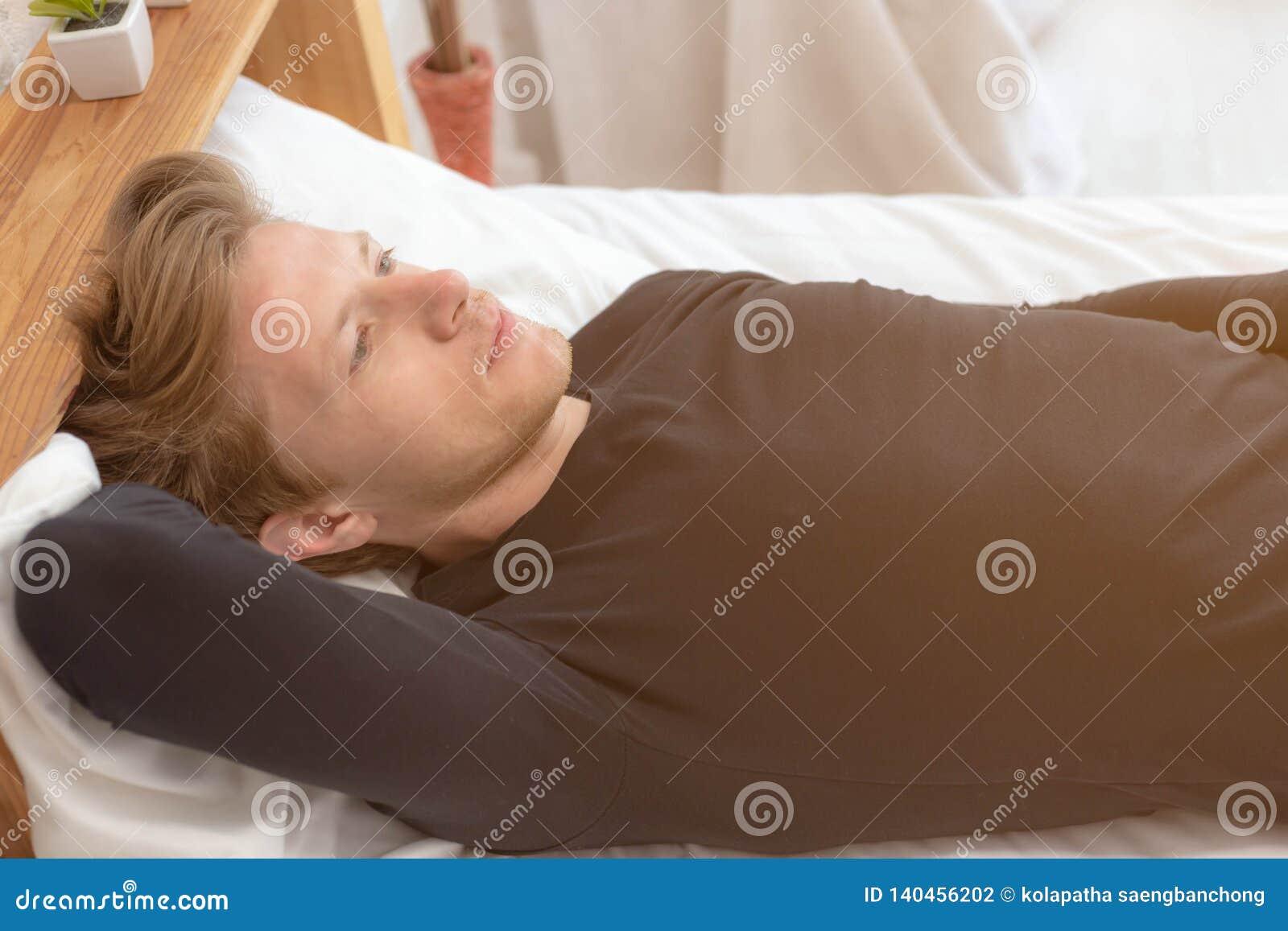 Jeune type beau de charme pensant quelque chose à sa future vie sur le lit à la chambre à coucher L homme bel attirant obtient so