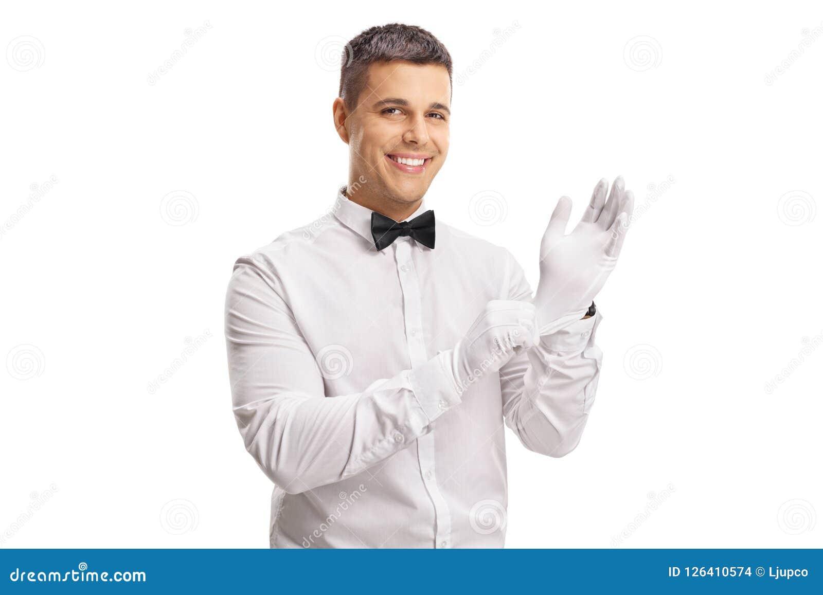 Jeune type dans un smoking mettant des gants