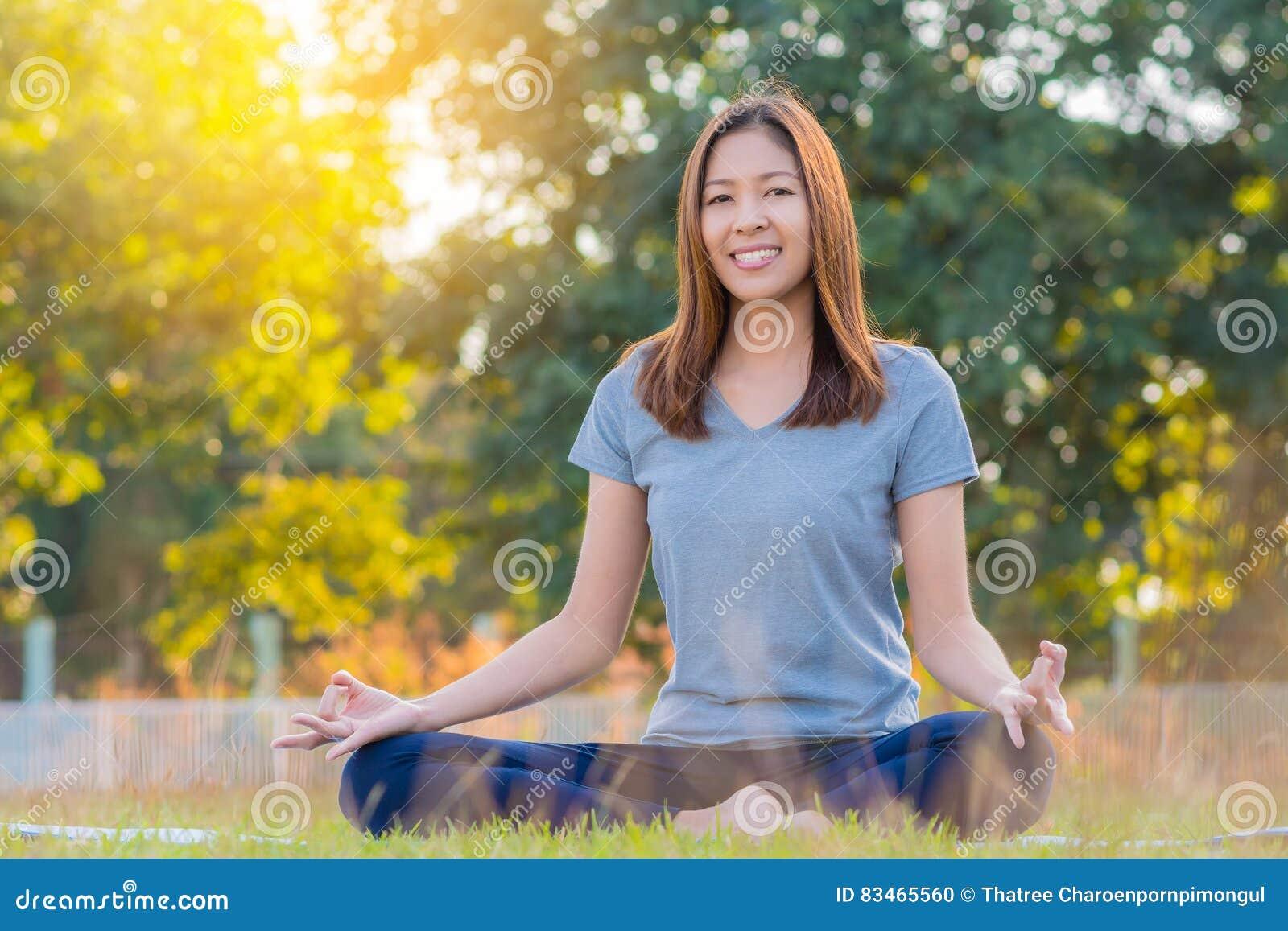 Jeune yoga de pratique de sourire asiatique de femme, se reposant dans la pose facile