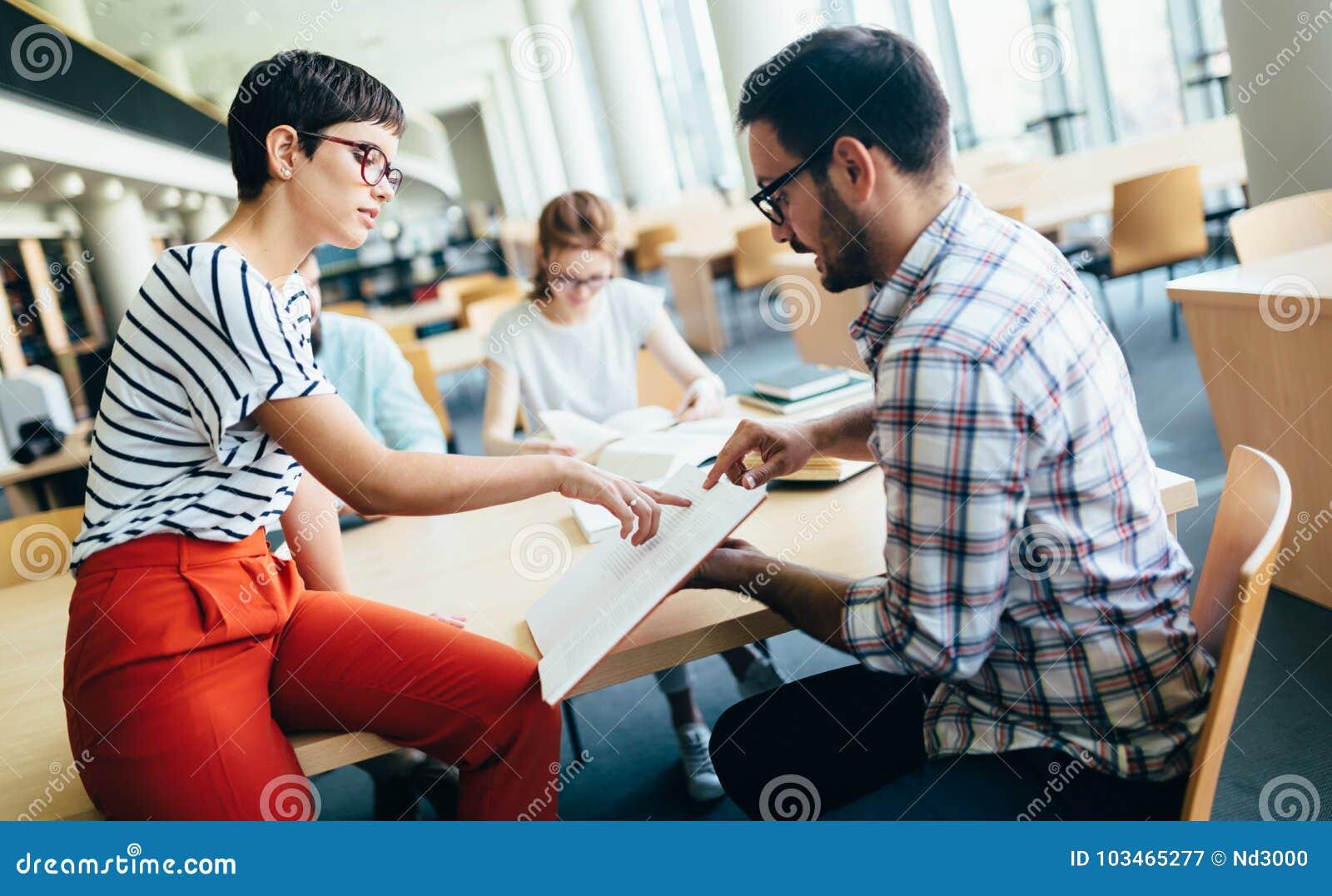 Jeunes étudiants attirants passant le temps dans la bibliothèque