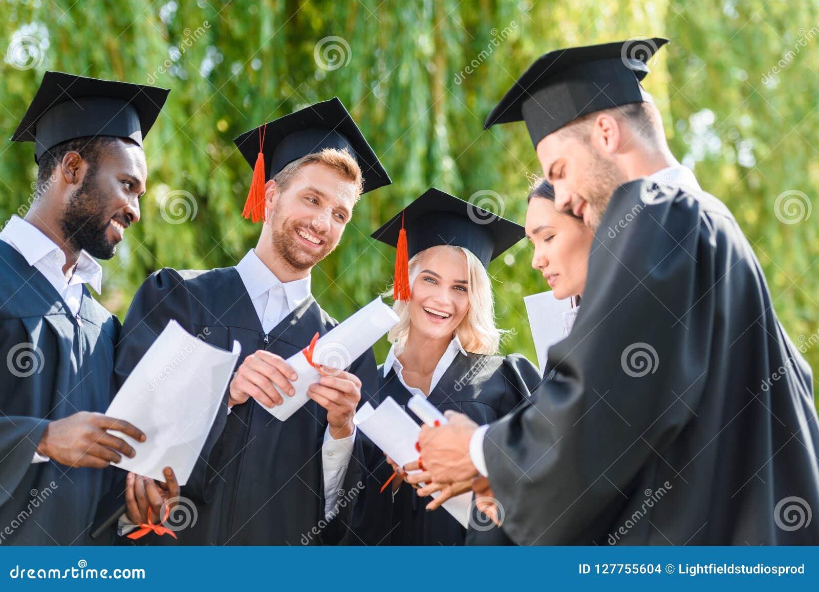 Jeunes étudiants gradués heureux dans les caps
