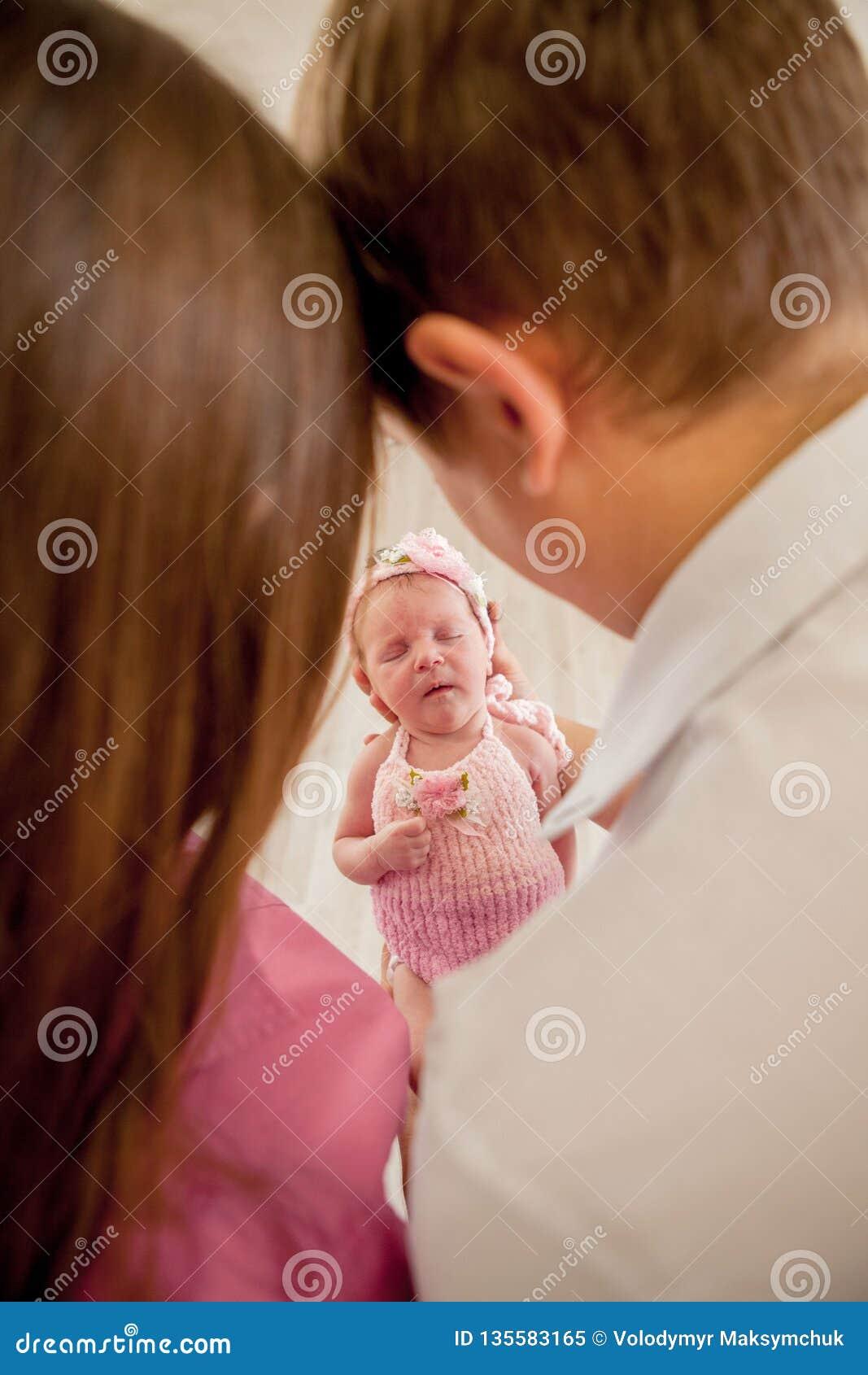 Jeunes ajouter au petit bébé mignon Mère et père de sourire tenant leur fille nouveau-née de bébé à la maison Accouplez les baise