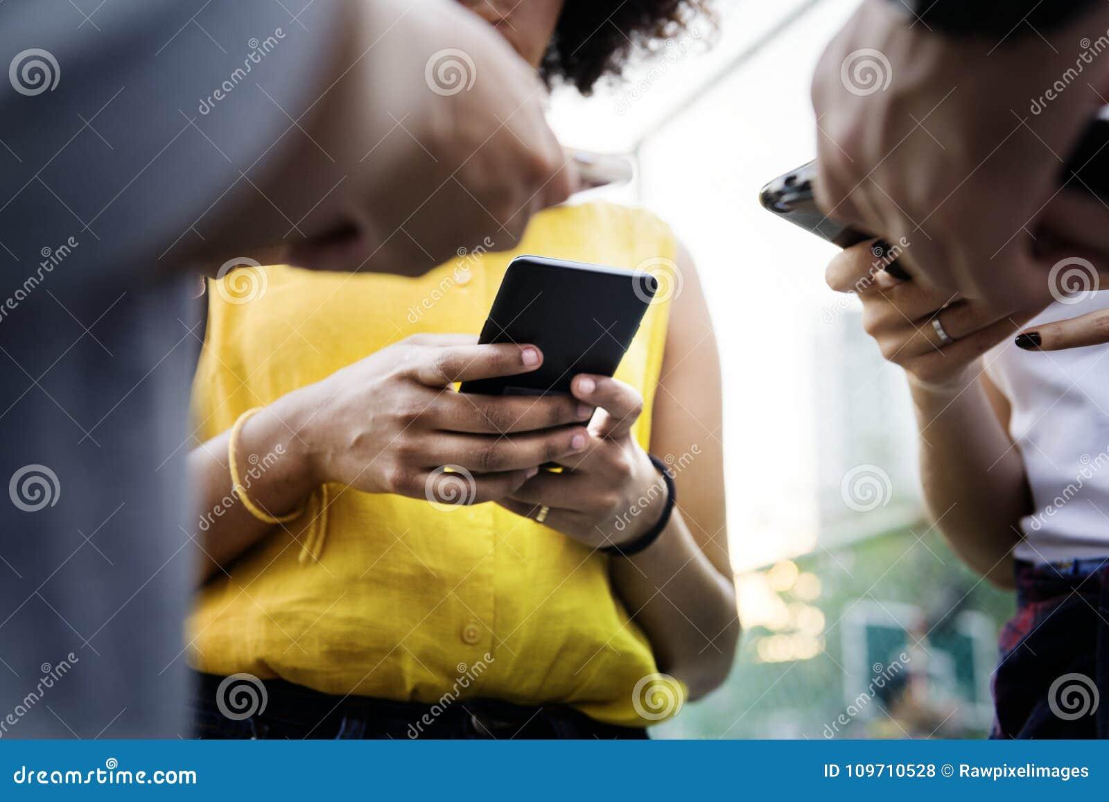 Jeunes amis adultes à l aide des smartphones dehors