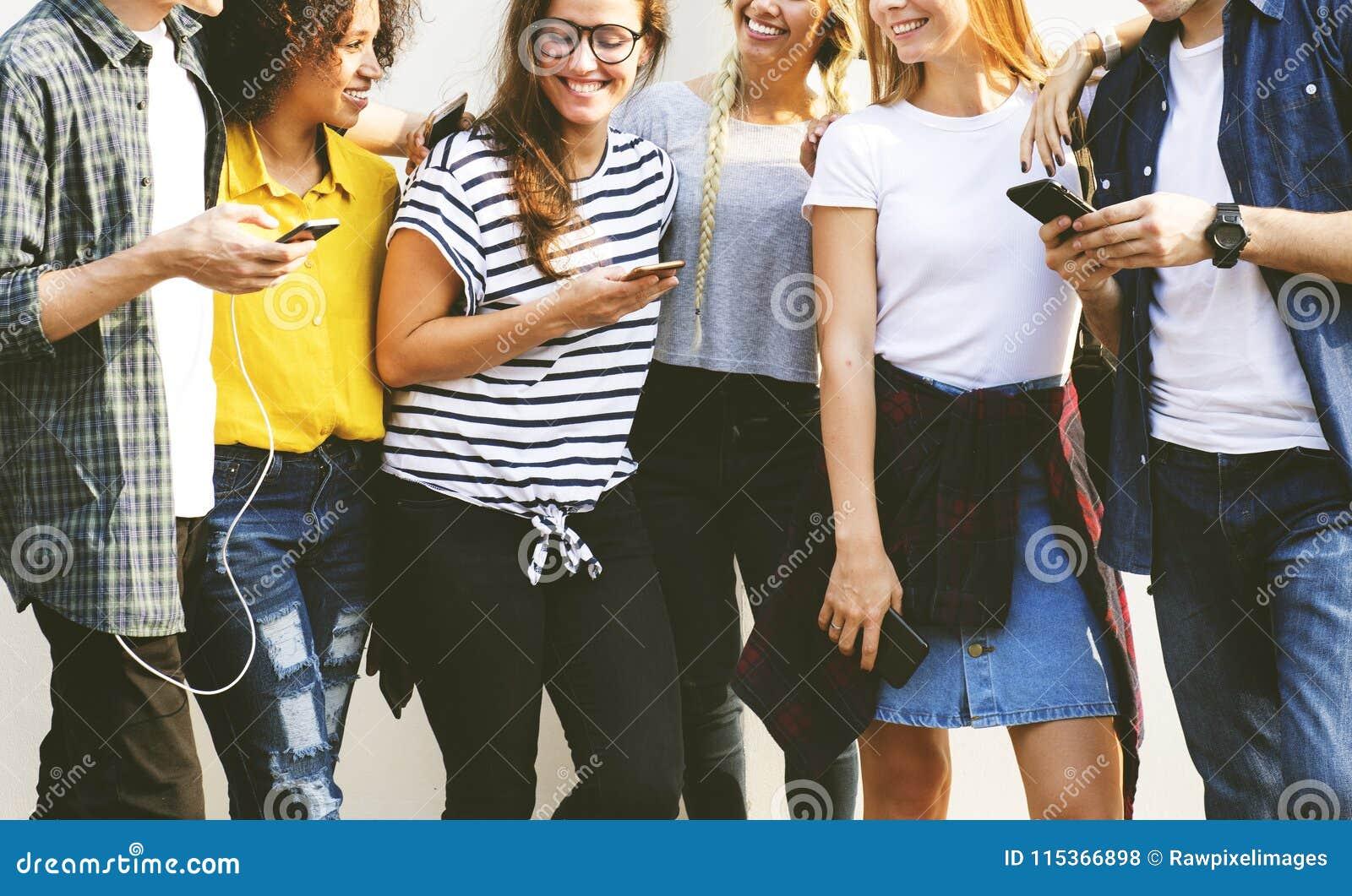 Jeunes amis adultes employant le Cu de la jeunesse de smartphones ensemble dehors