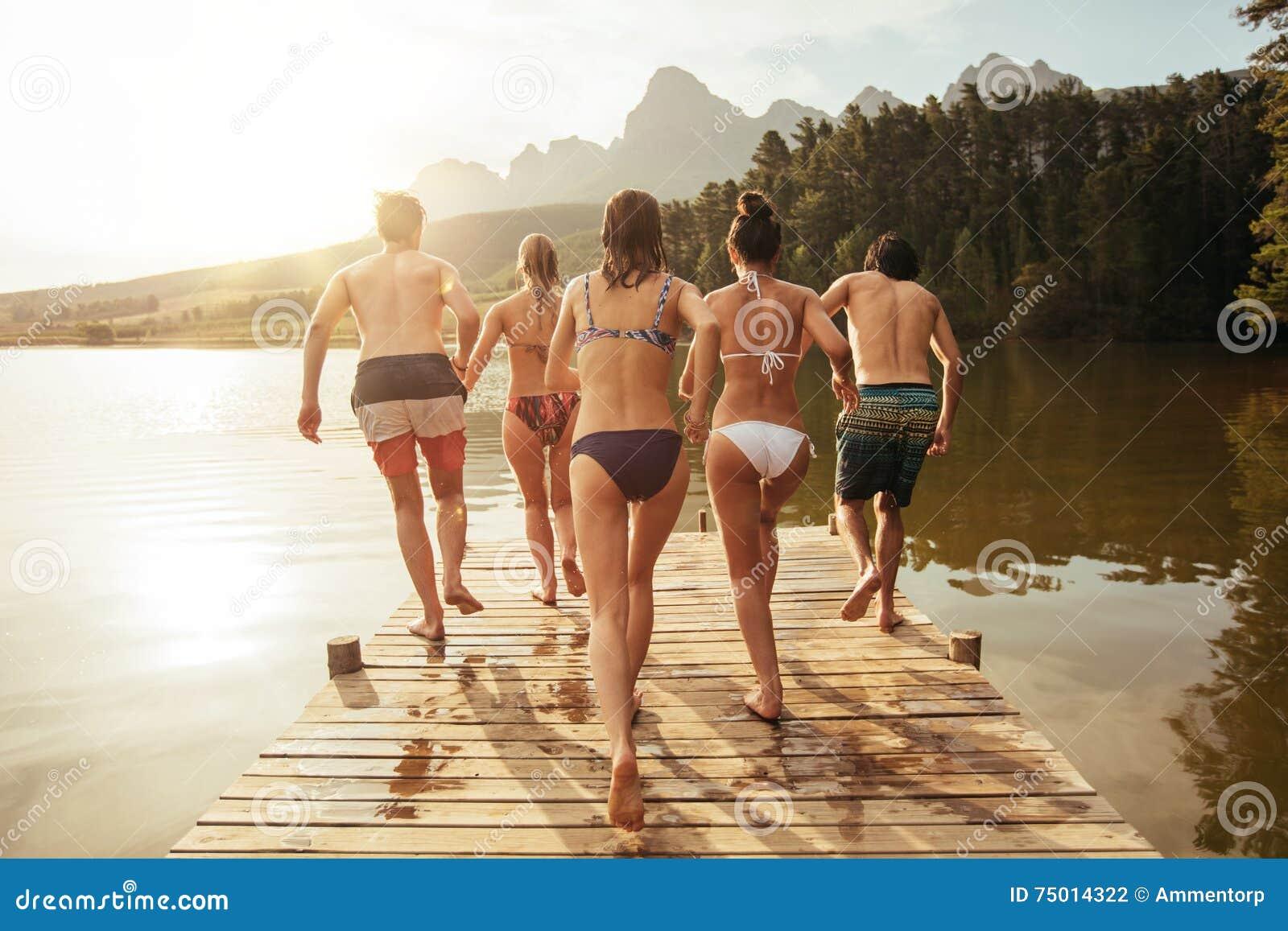 Jeunes amis environ à sauter dans le lac d un pilier