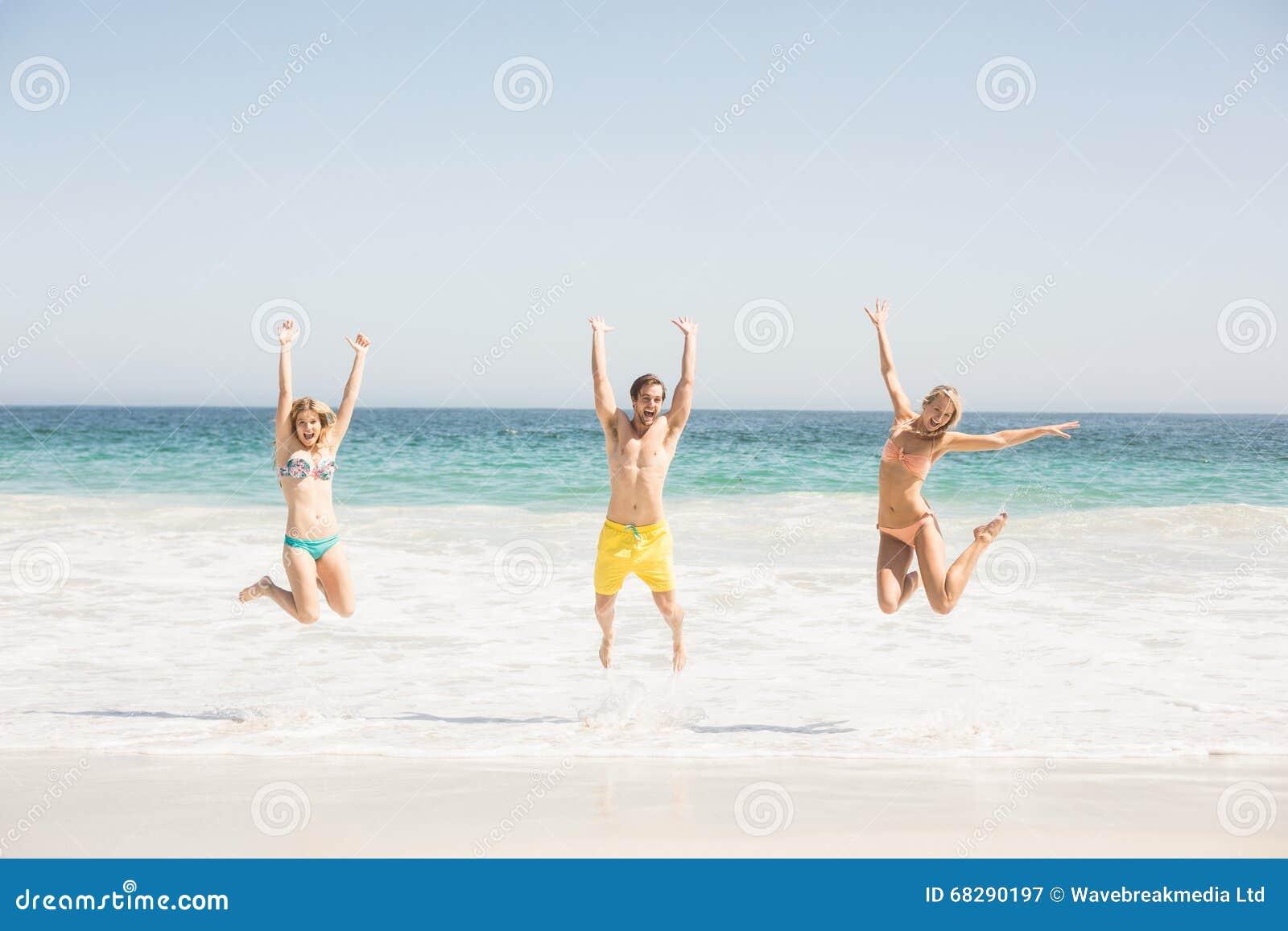 Jeunes amis heureux sautant sur la plage