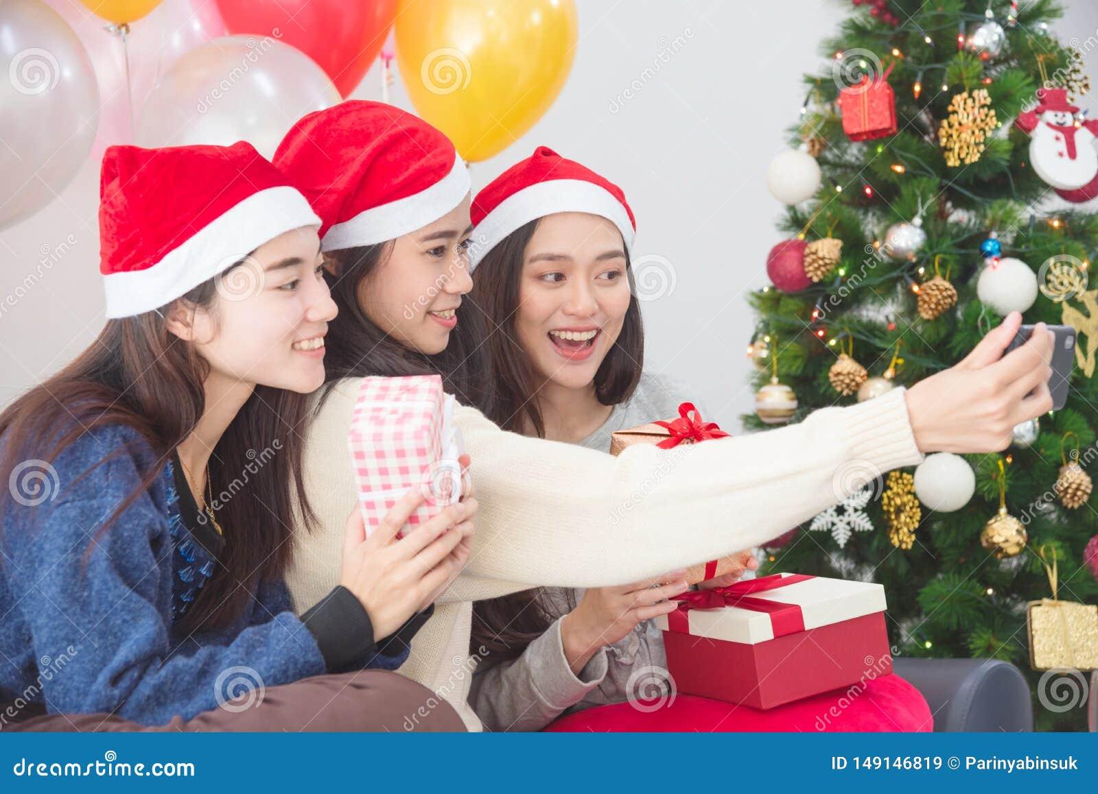 Jeunes asiatiques prenant la photo par le téléphone portable à la fête de Noël