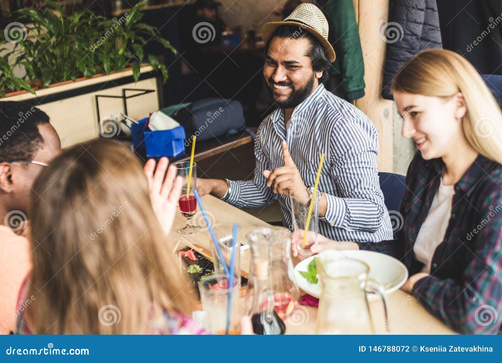 Jeunes attirants de rassemblement dans le caf? Les amis causent, ont l amusement, cocktails de boissons et mangent