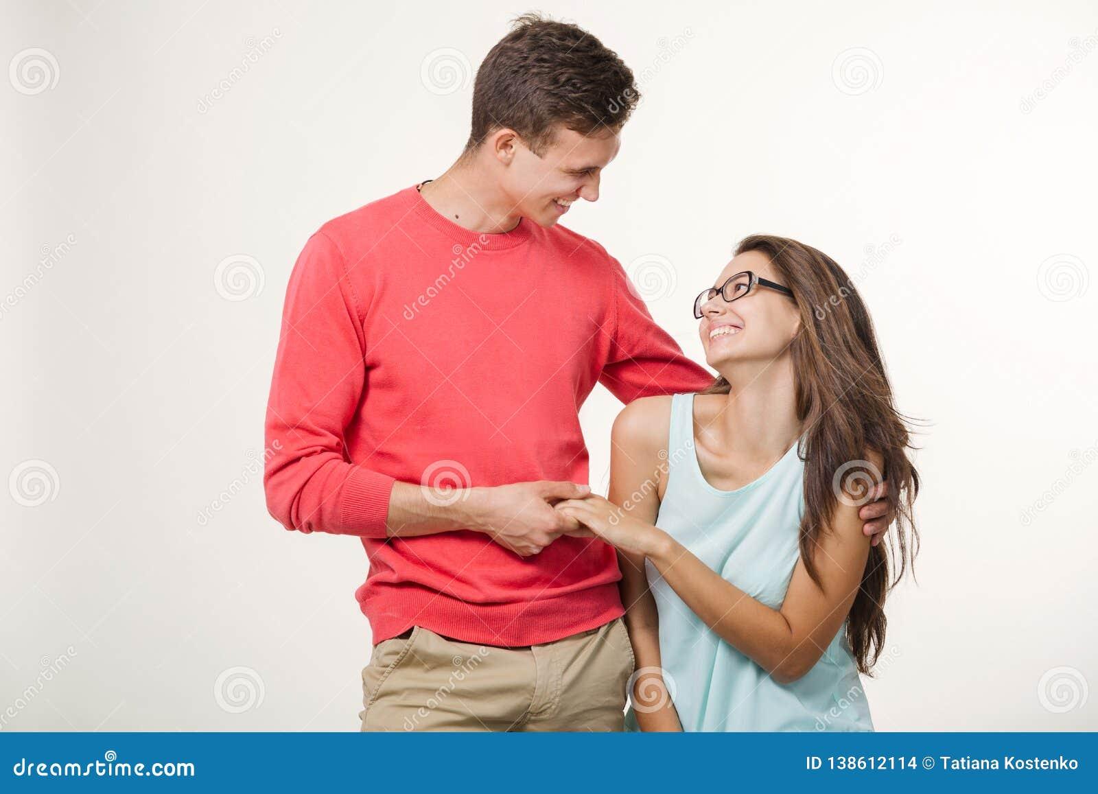 Jeunes beaux couples heureux se tenant ensemble et riant Le studio a tiré au-dessus du fond blanc Amitié, amour et