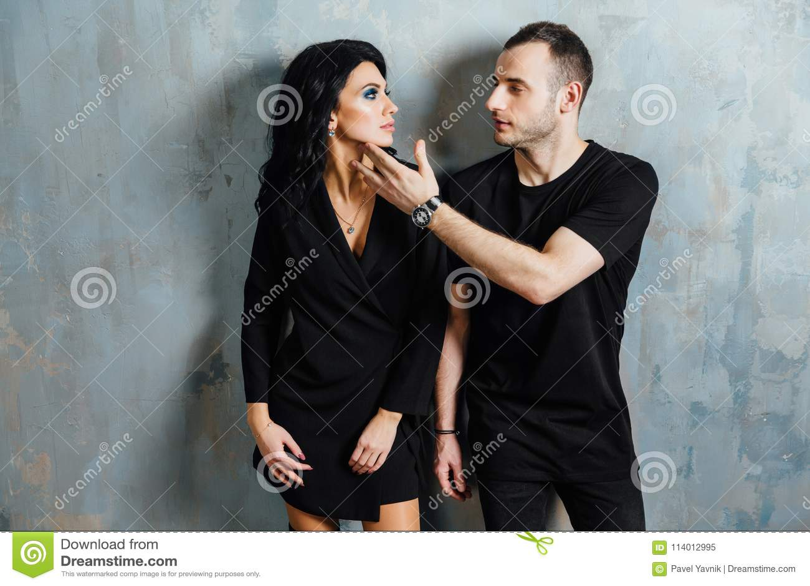 Jeunes beaux couples magnifiques élégants, contre le grenier gris de mur dans le studio ou à la maison