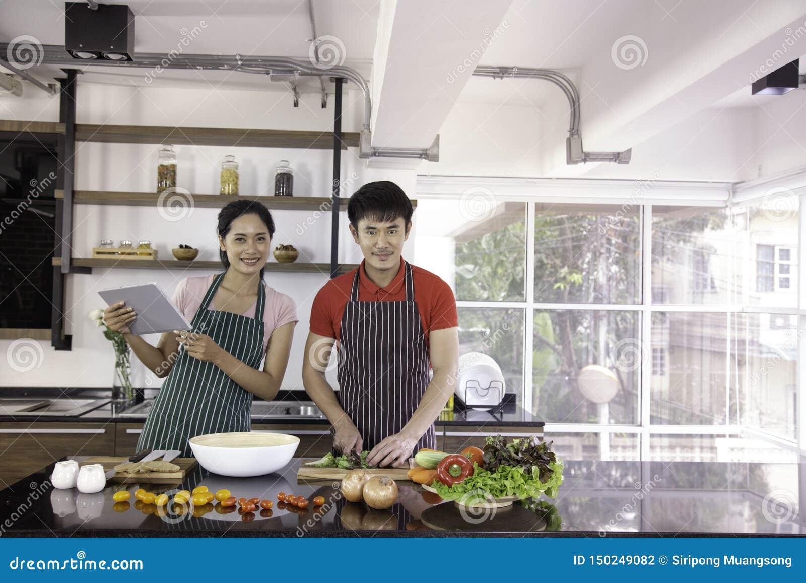 Jeunes beaux couples romantiques faisant cuire la nourriture dans la cuisine