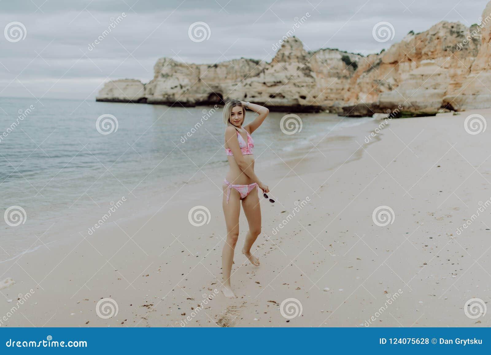 Jeunes belle femme mince sur la plage de coucher du soleil, espiègle, danse, courante et avoir l amusement
