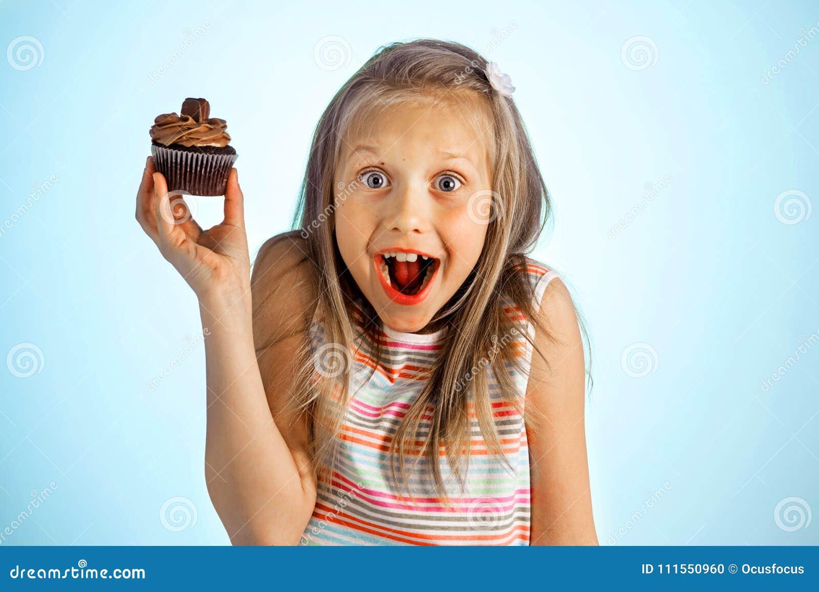 Jeunes belles années blondes heureuses et enthousiastes folles de la fille 8 ou 9 tenant le beignet sur sa main semblant spastiqu