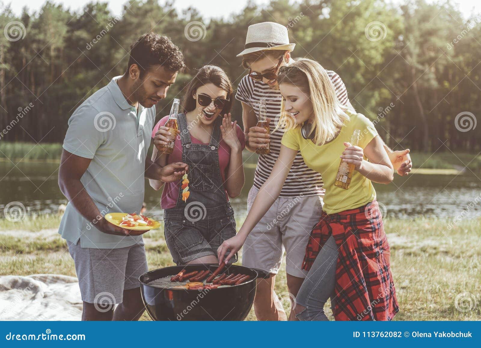 Jeunes casse-croûte de réjouissance de bière de torréfaction de société dans la forêt
