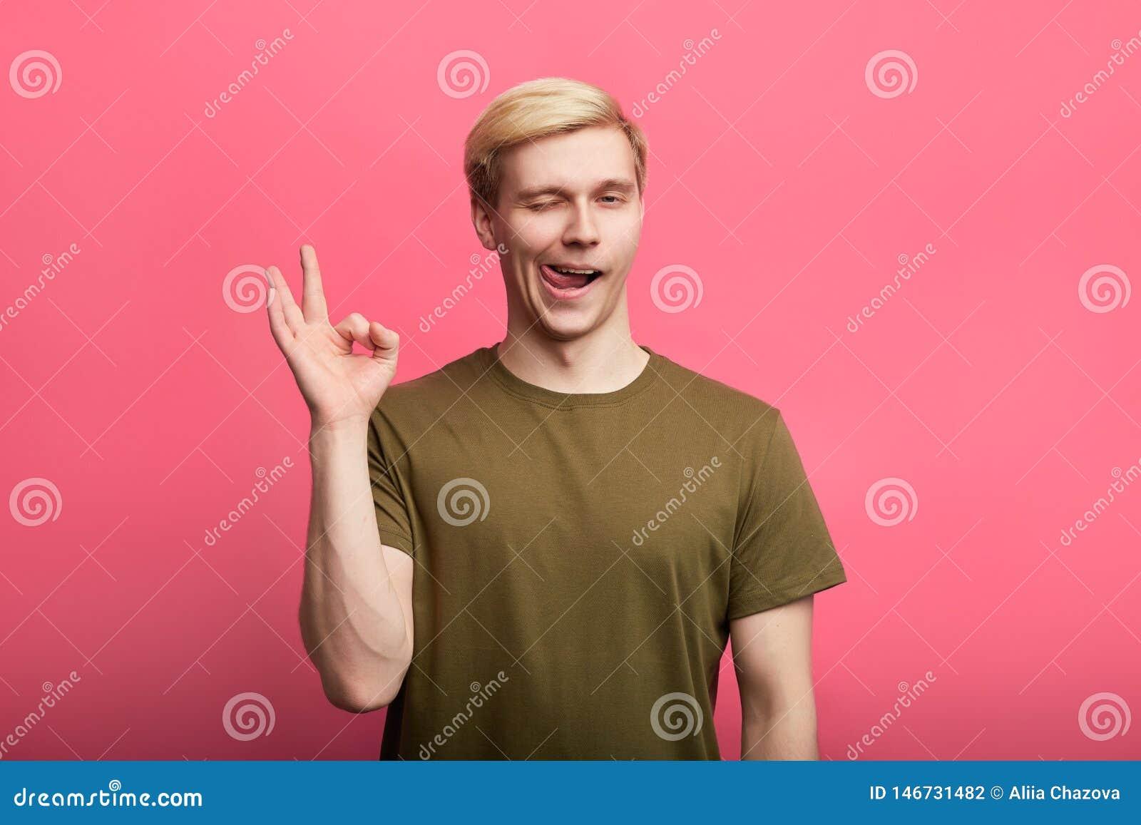 Jeunes clins d oeil avec du charme amicaux de type tout en montrant le geste CORRECT, d isolement sur le fond rose