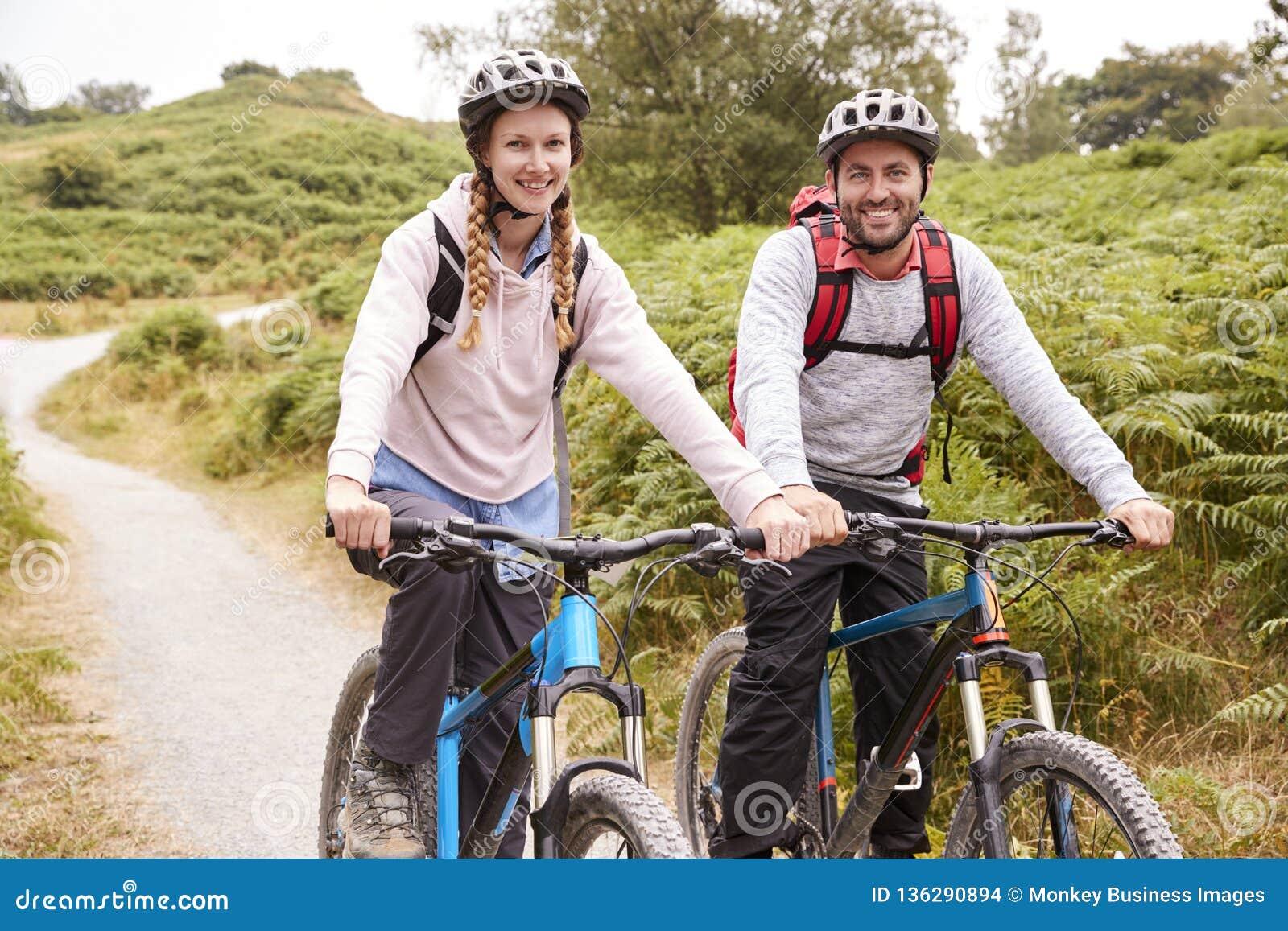 Jeunes couples adultes se reposant sur des vélos de montagne dans une ruelle de pays pendant des vacances campantes, fin