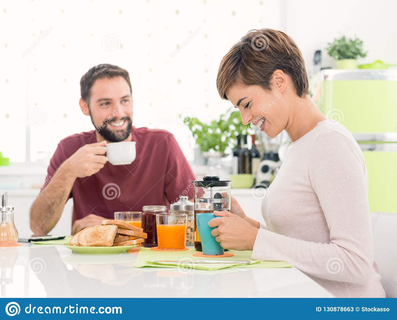 Jeunes couples affectueux prenant le petit déjeuner à la maison
