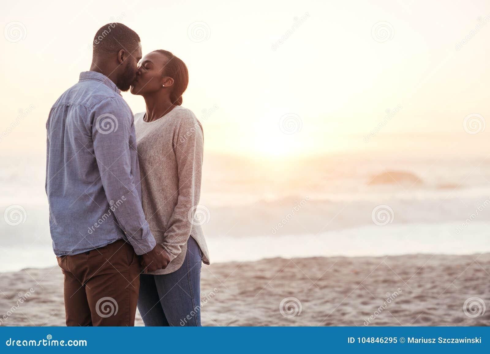 Jeunes couples africains romantiques embrassant sur une plage au coucher du soleil