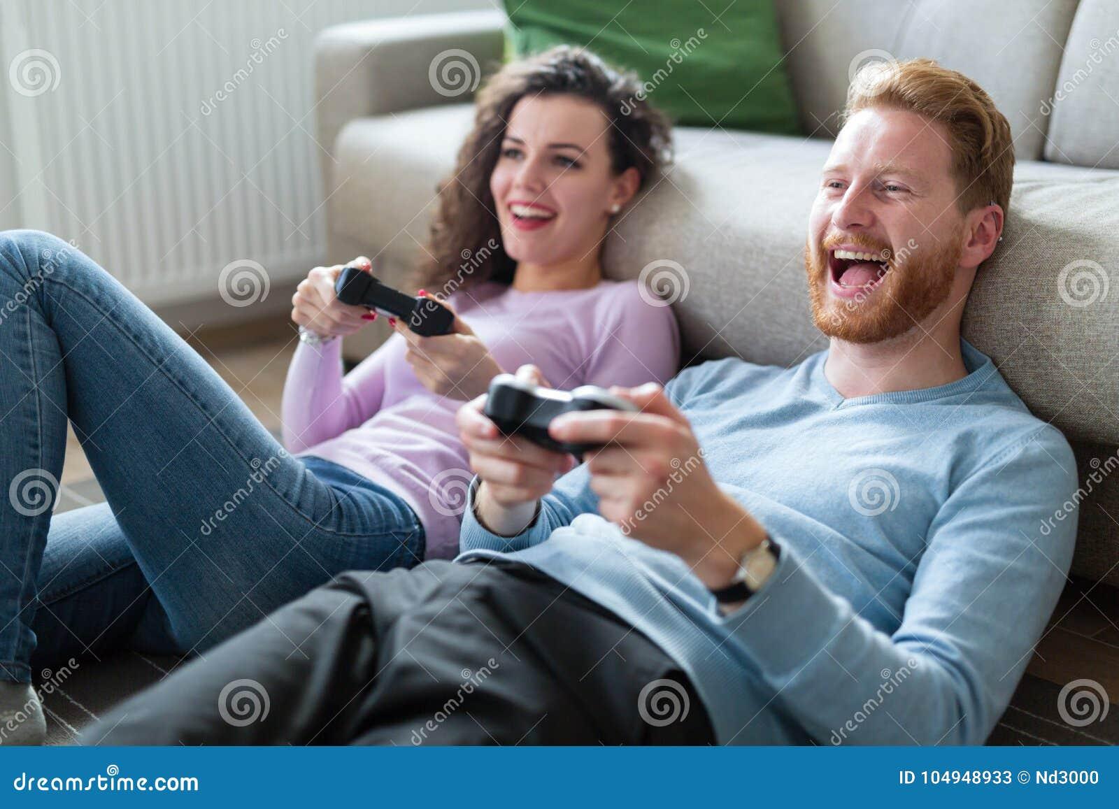 Jeunes couples ayant l amusement jouant des jeux vidéo