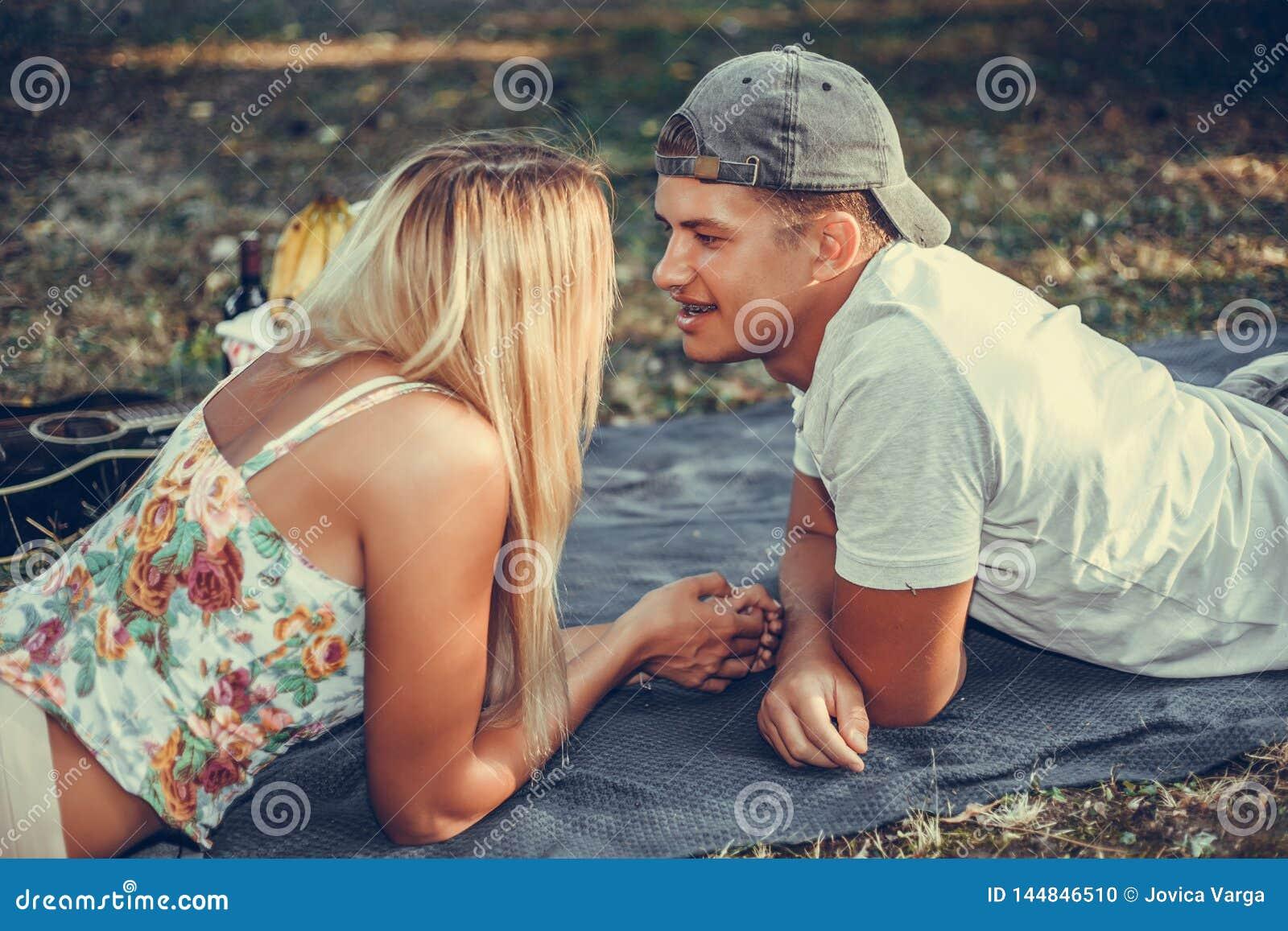 Jeunes couples ayant un pique-nique se trouvant sur la couverture sur la pelouse regardant l un l autre