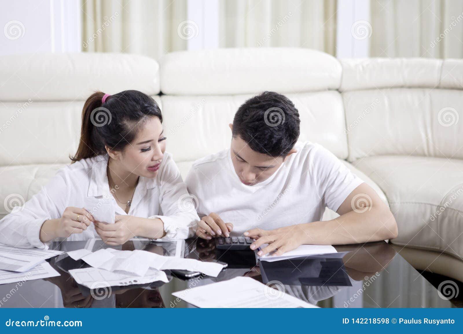 Jeunes couples calculant leurs finances de ménage