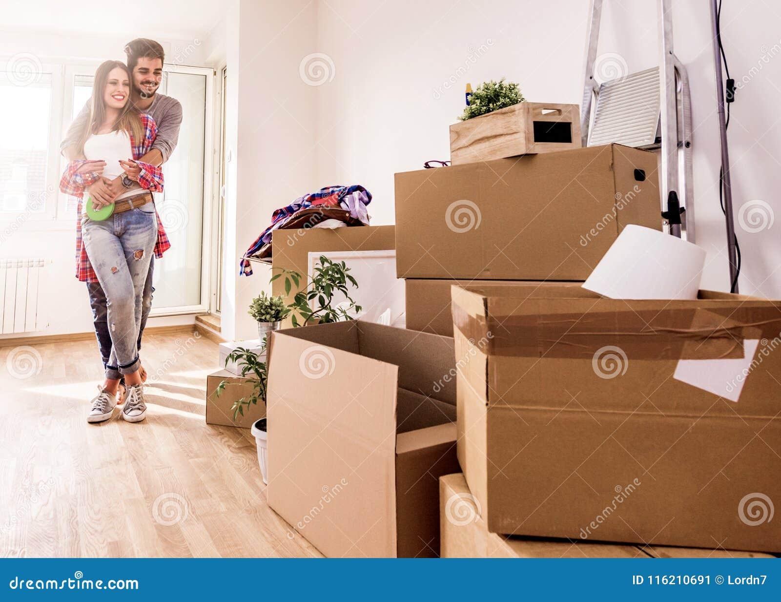 Jeunes couples déménageant la maison neuve Déballage des récipients de boîte et nettoyage