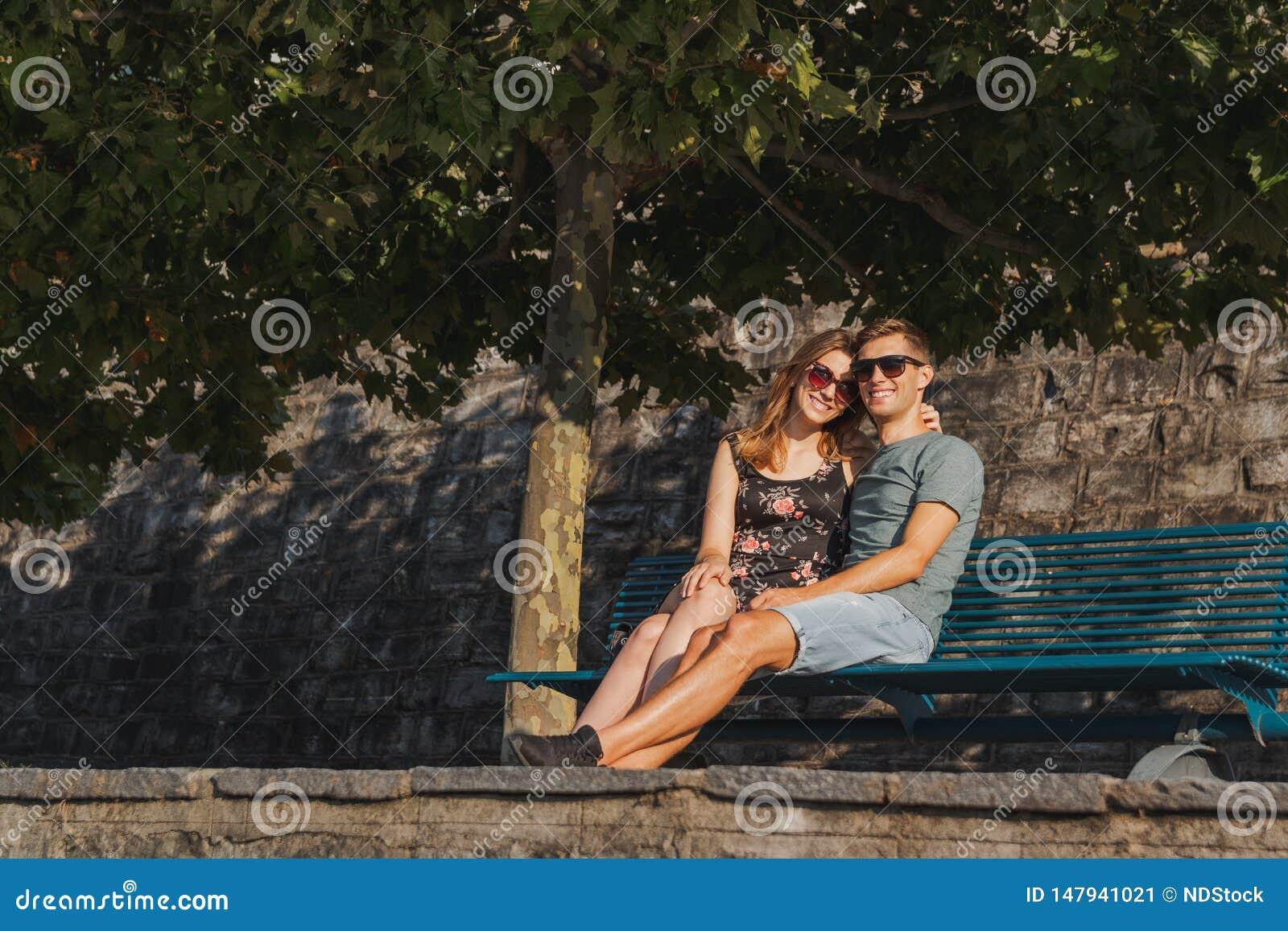 Jeunes couples dans l amour pos?s sur un banc et d?tendre pendant un jour ensoleill?