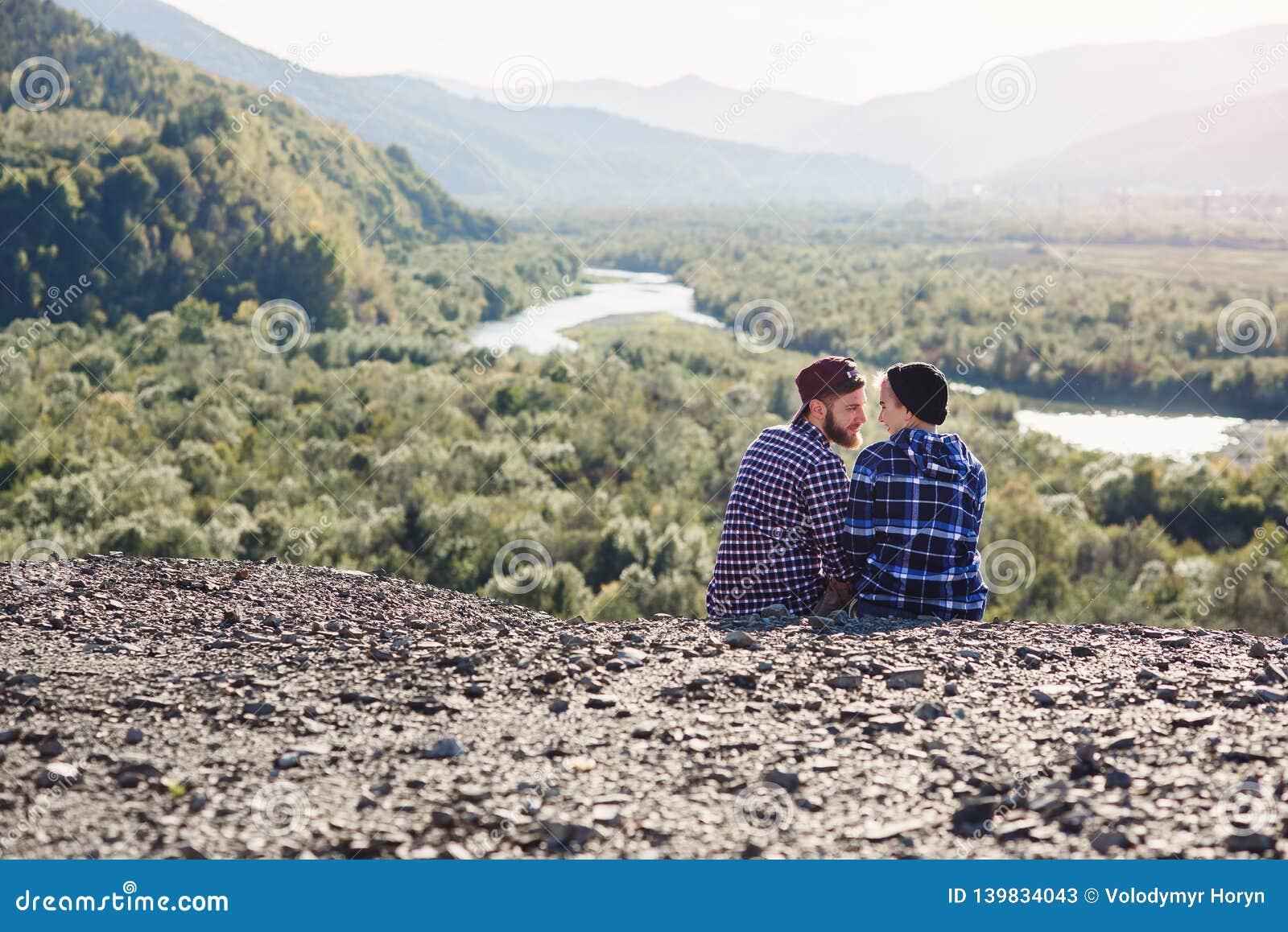 Jeunes couples dans l amour voyageant ensemble en montagnes Homme heureux et fille de hippie s asseyant ensemble sur le dessus de