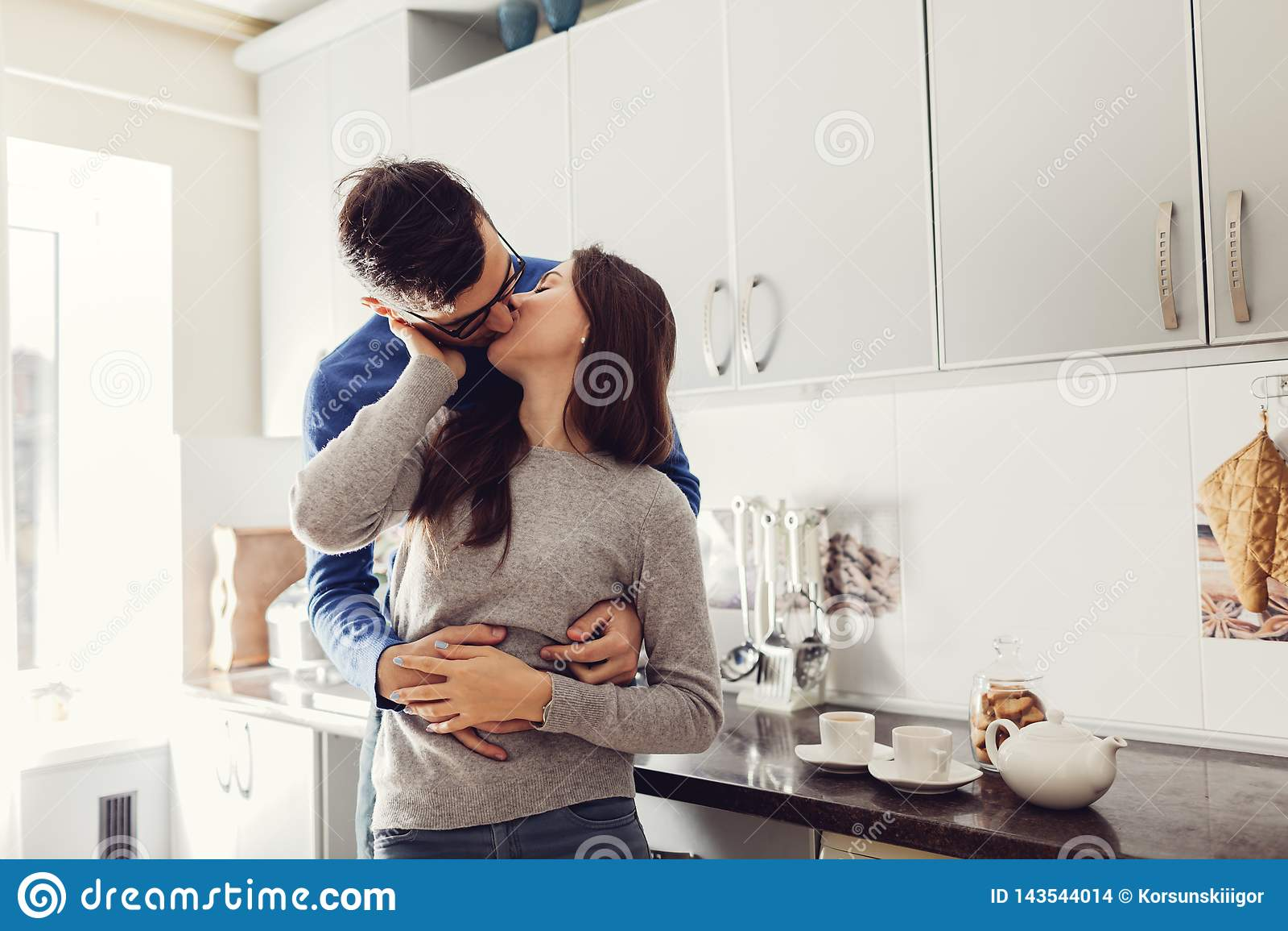 Jeunes couples dans la cuisine étreignant et embrassant