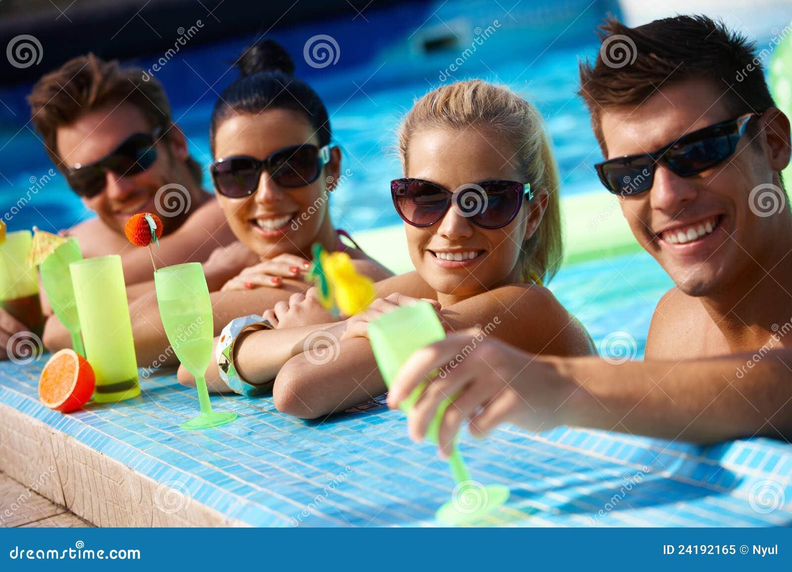 Jeunes couples dans la piscine avec le cocktail