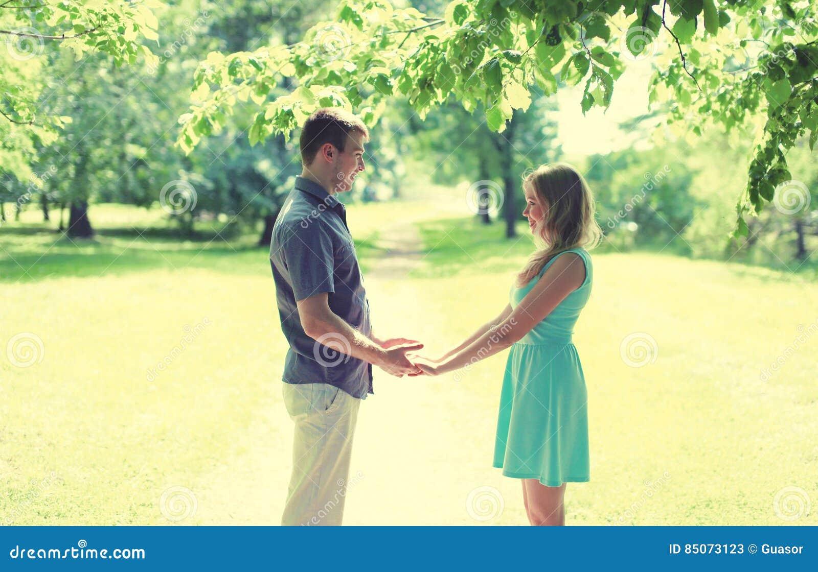 Jeunes couples de sourire heureux dans l amour, mains de prises, relations, date, épousant - concept, couleurs douces de vintage