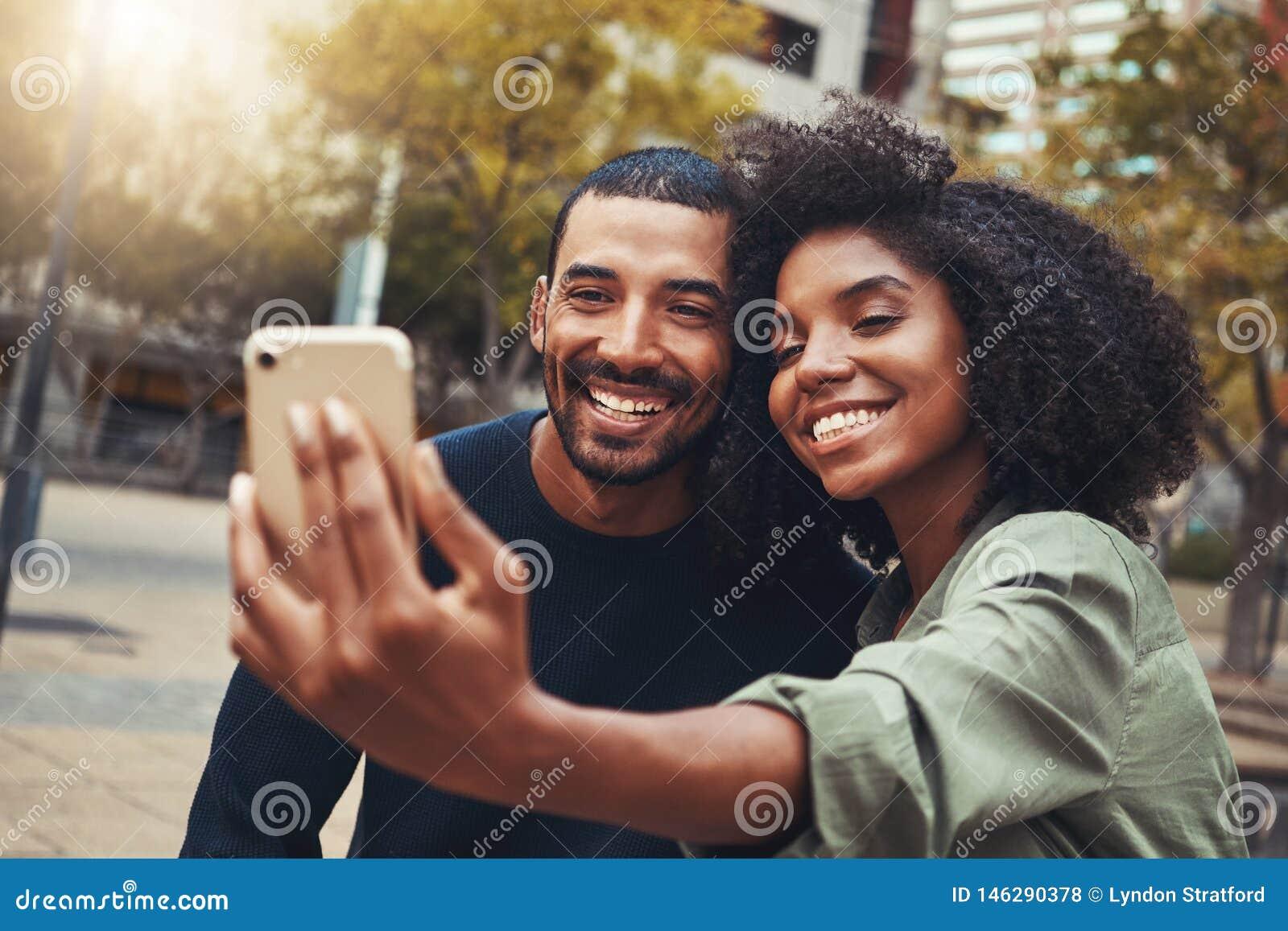 Jeunes couples de sourire prenant le selfie en parc de ville