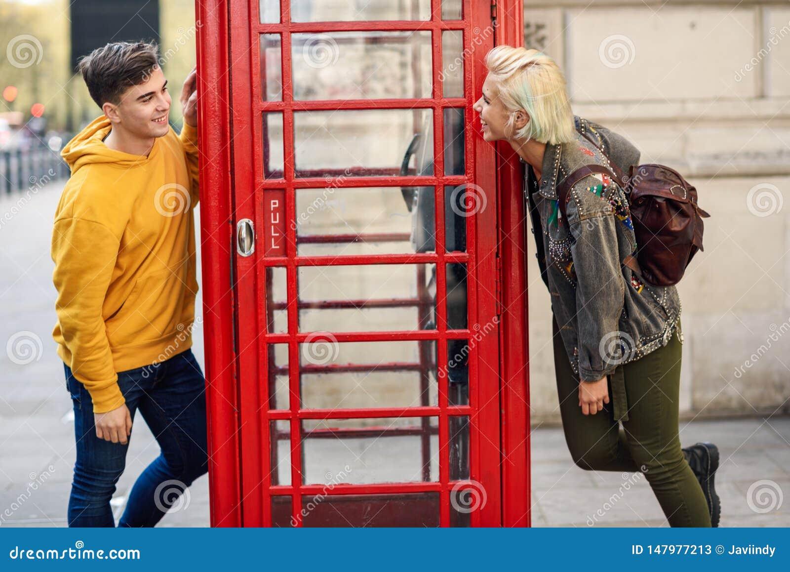 Jeunes couples des amis près d une cabine de téléphone rouge britannique classique