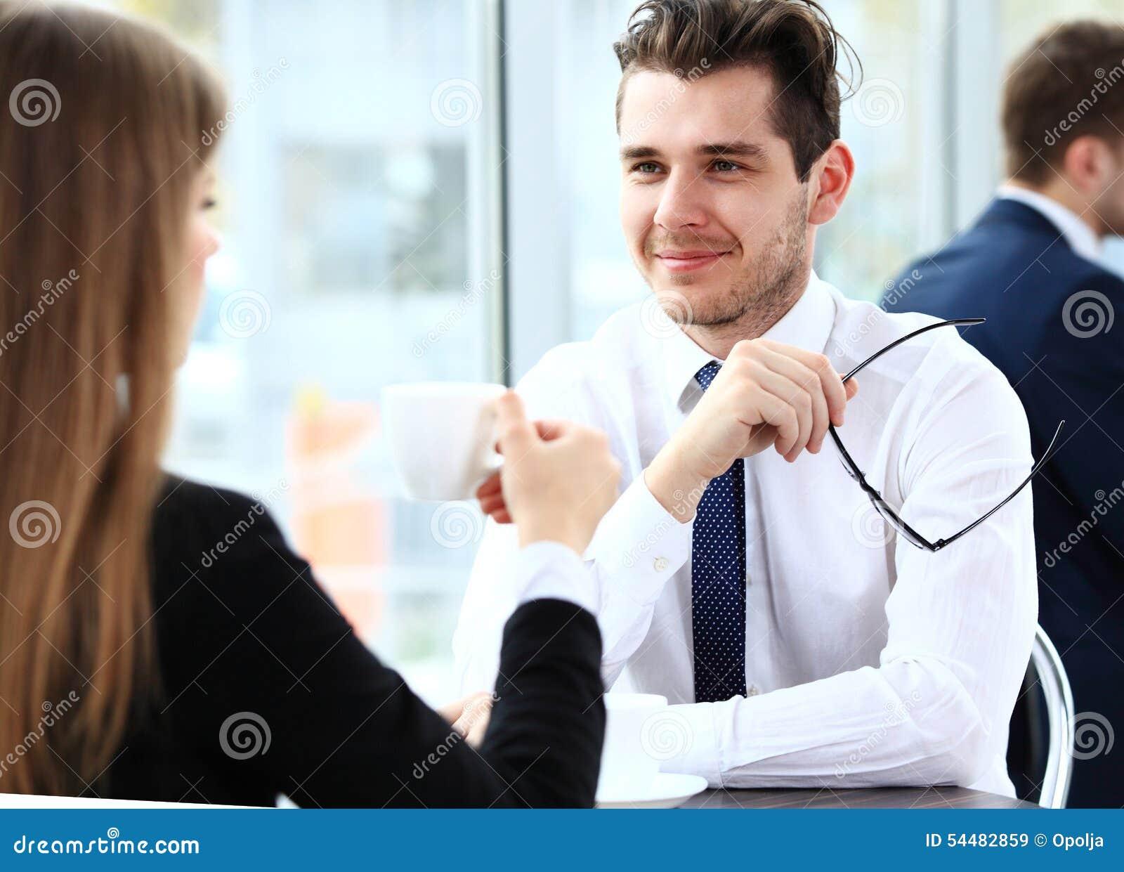 Jeunes couples des professionnels causant pendant un coffeebreak