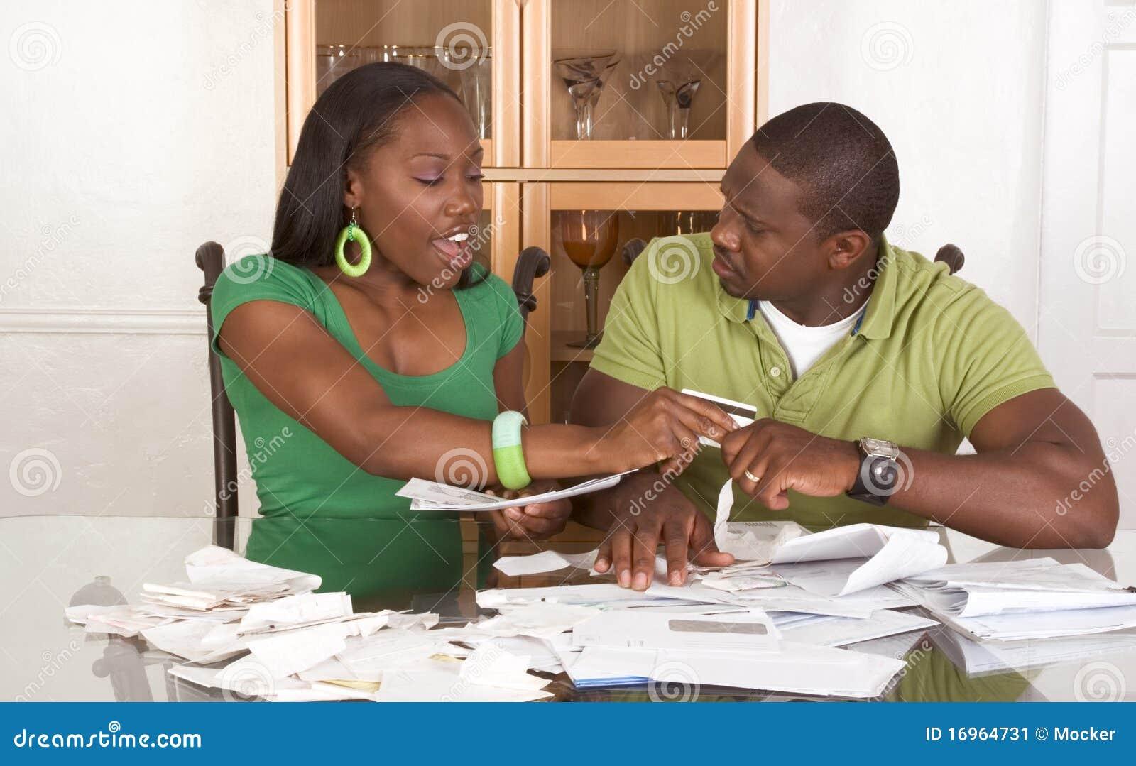 Jeunes couples ethniques par la table accablée par des factures
