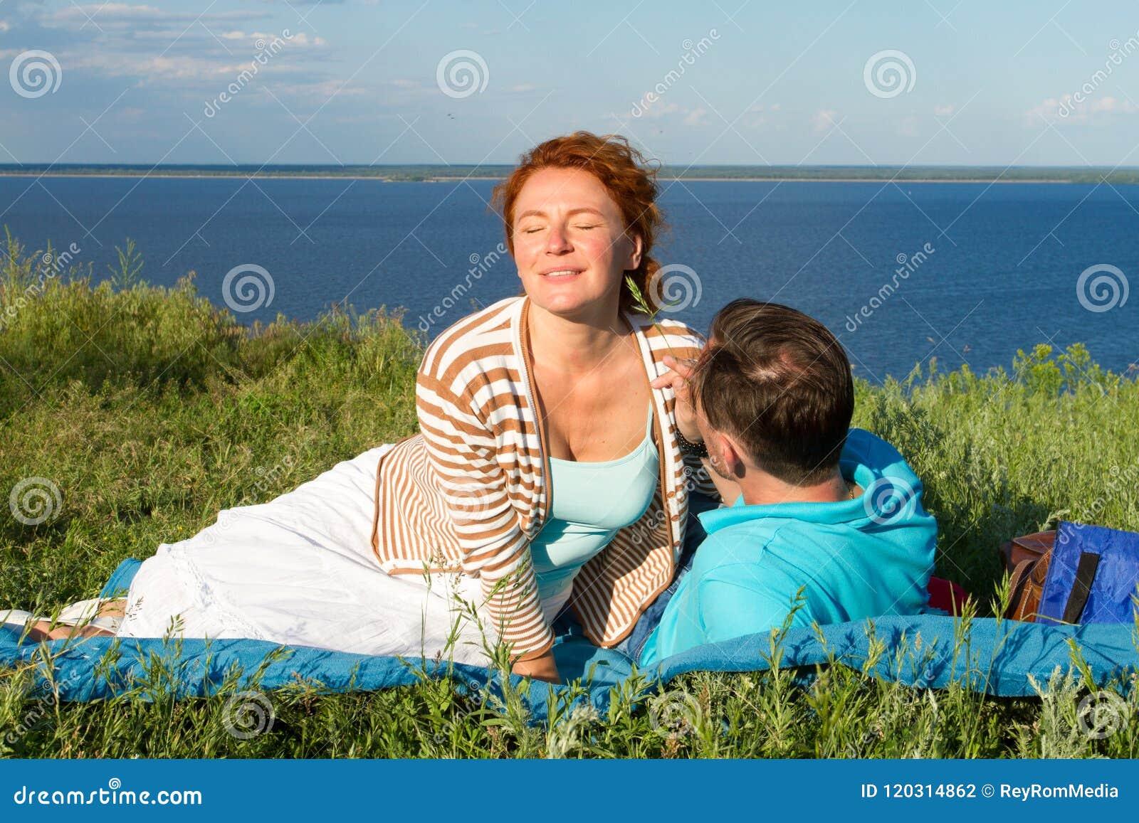 Jeunes couples heureux ayant l amusement dehors et le sourire Beaux couples s étendant sur la plage le soir
