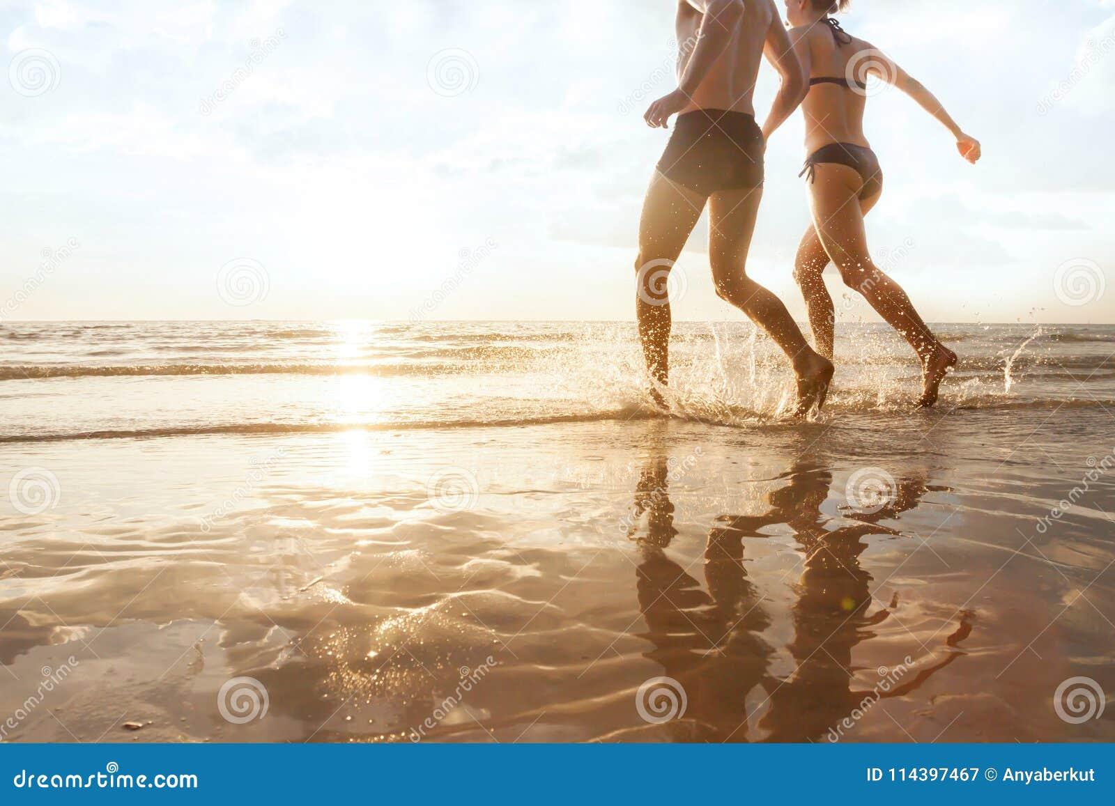 Jeunes couples heureux fonctionnant à la mer sur la plage au coucher du soleil, aux silhouettes de l homme et à la femme