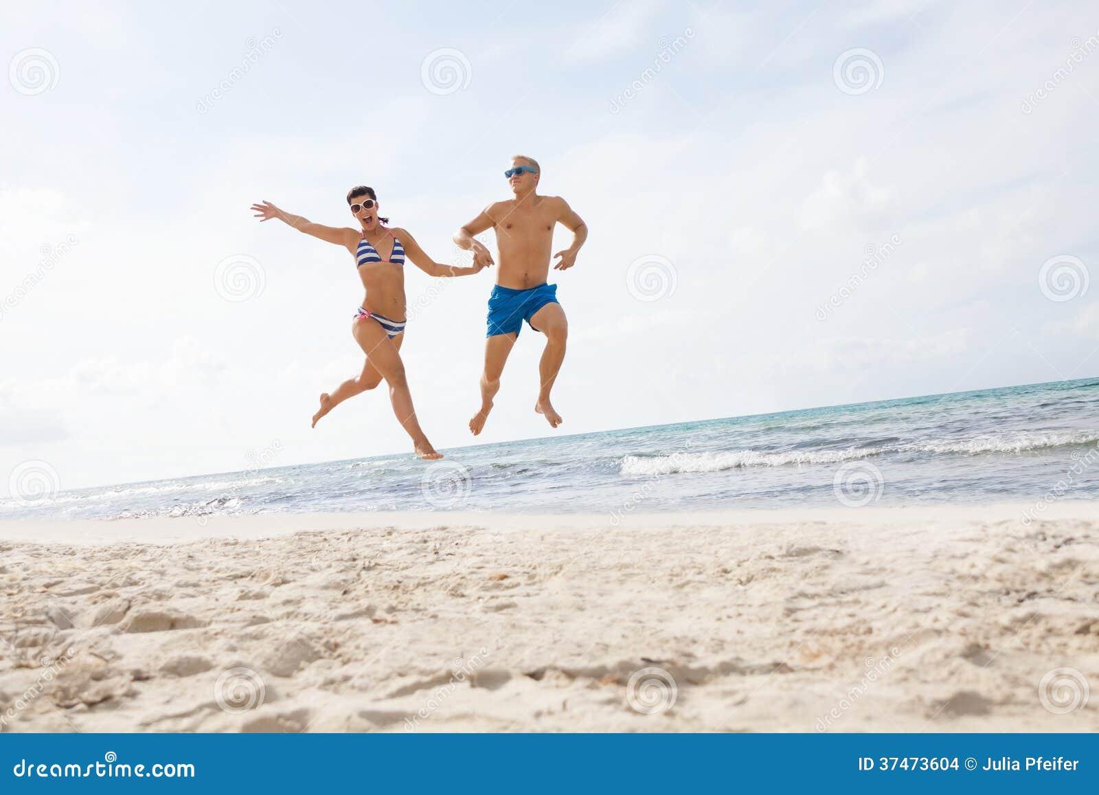 Jeunes couples heureux marchant des vacances de coucher du soleil de plage