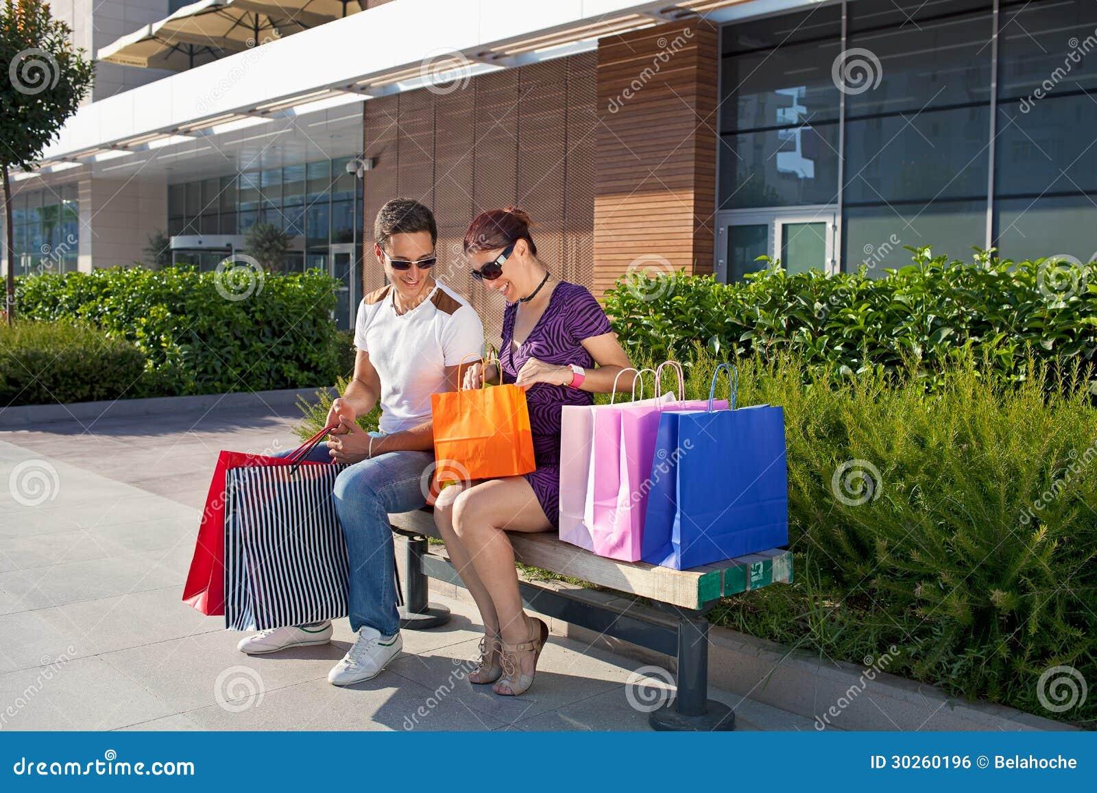Jeunes couples gais détendant, sacs à provisions colorés de transport.