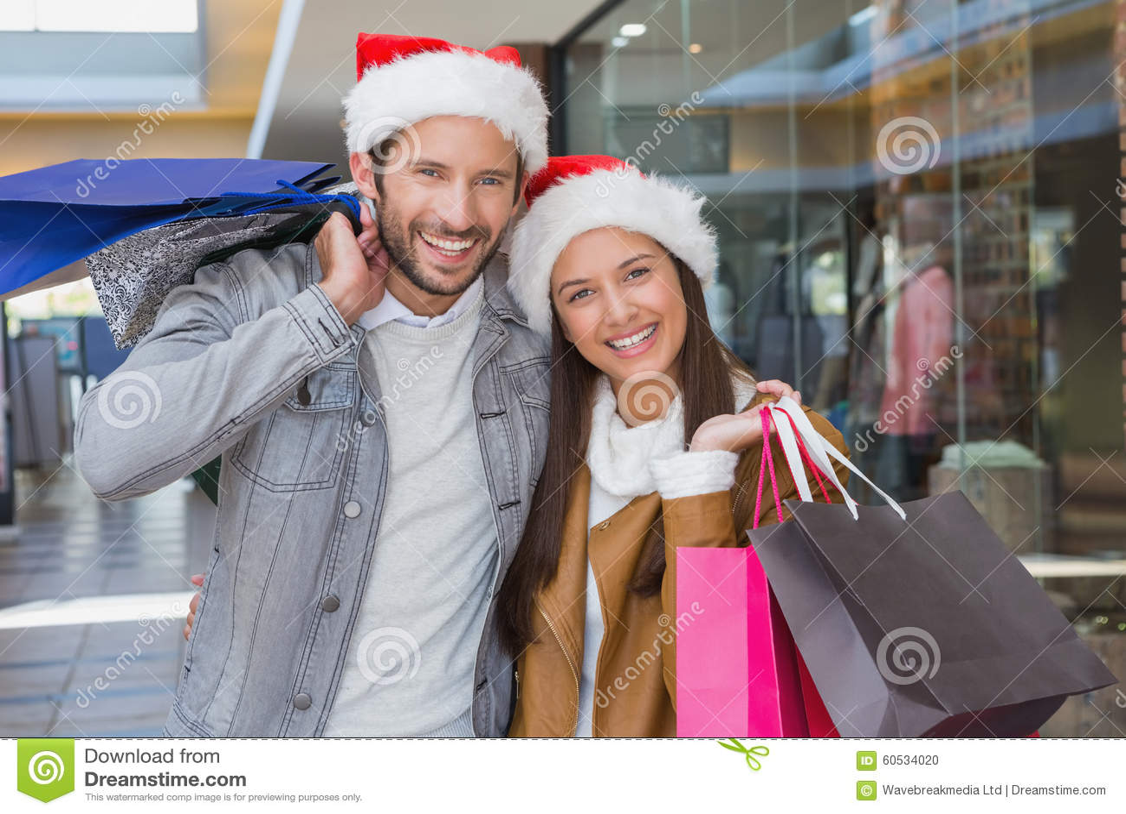 Jeunes couples heureux tenant des paniers avec des chapeaux de Noël sur leurs chapeaux