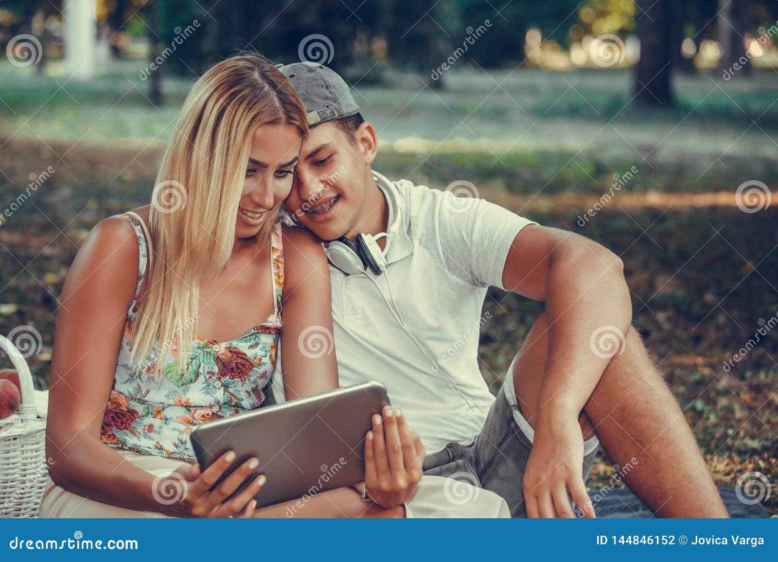 Jeunes couples heureux utilisant le comprimé numérique pendant le pique-nique en parc