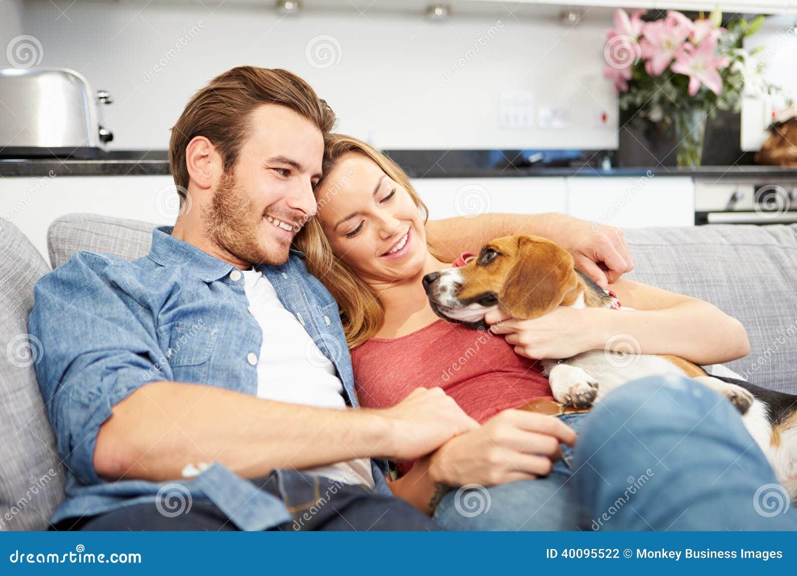 Jeunes couples jouant avec le chien à la maison