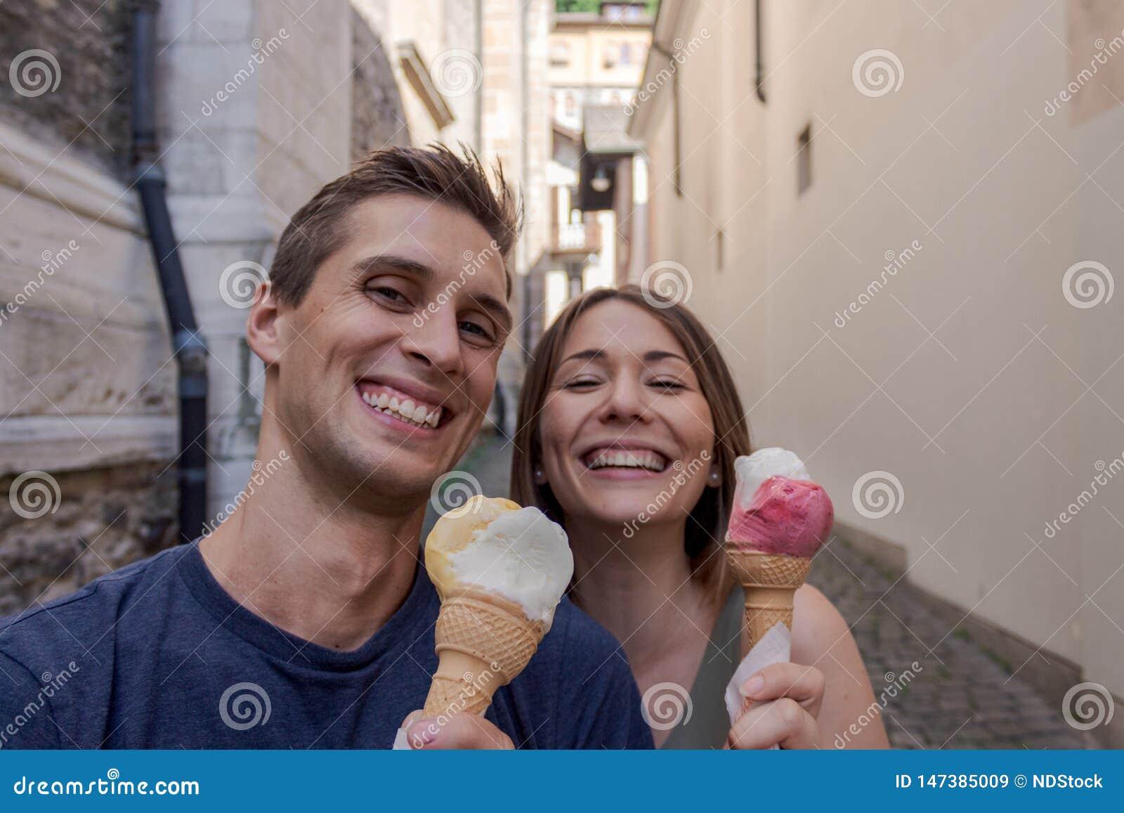 Jeunes couples mangeant la cr?me glac?e dans une all?e