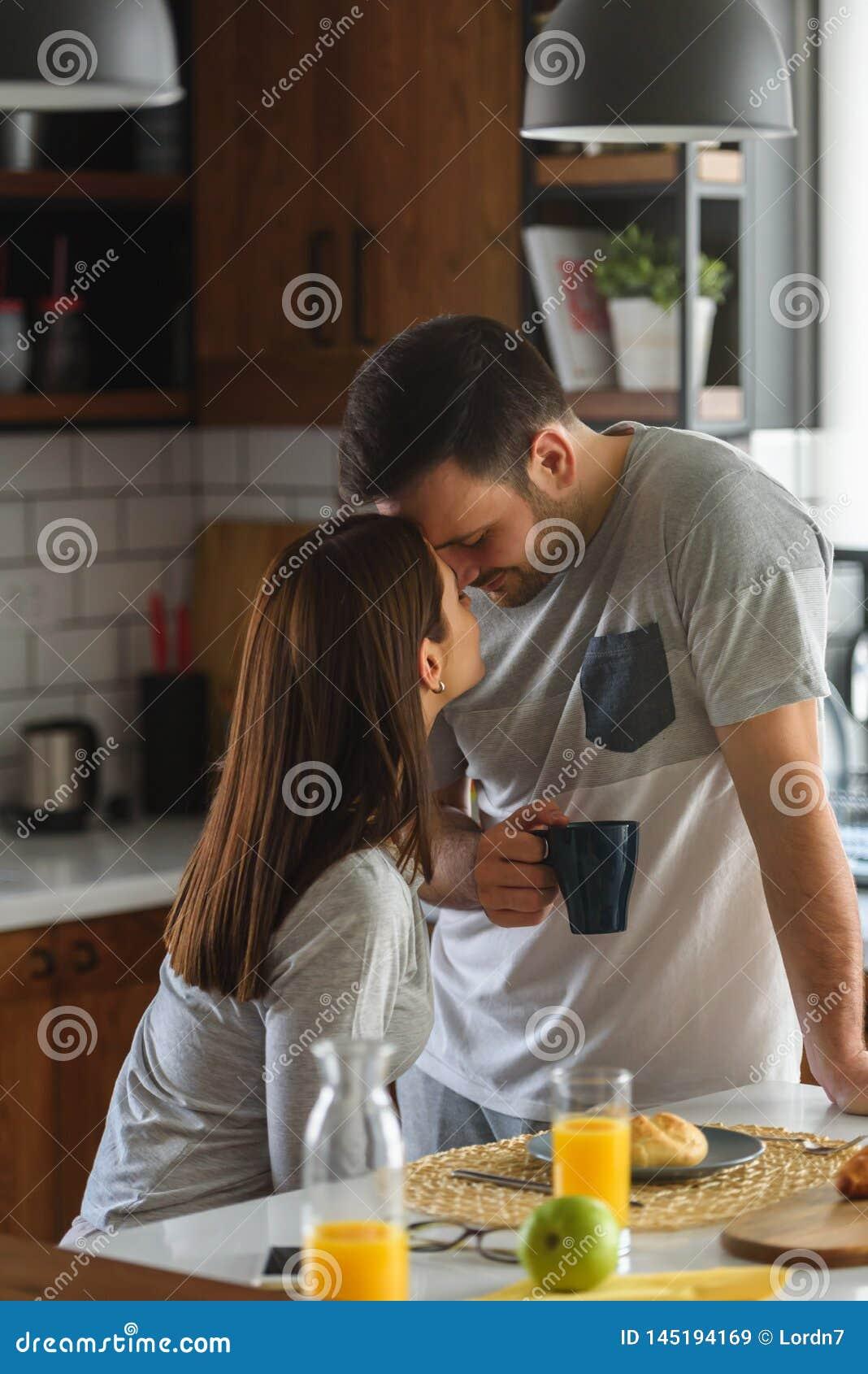 Jeunes couples mariés beaux prenant le petit déjeuner pendant le matin à la maison dans leurs pyjamas