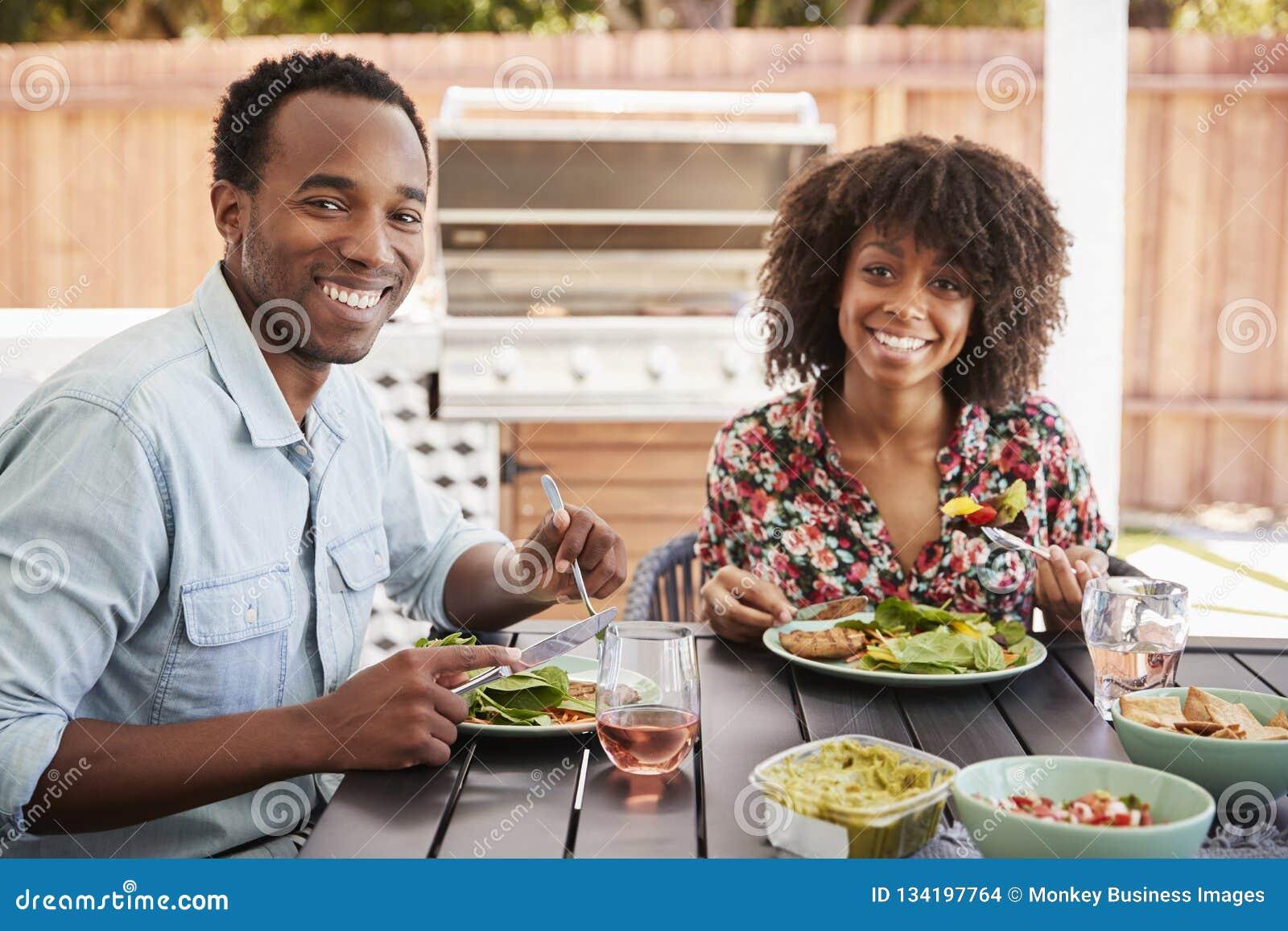 Jeunes couples noirs mangeant dans le jardin regardant à la caméra
