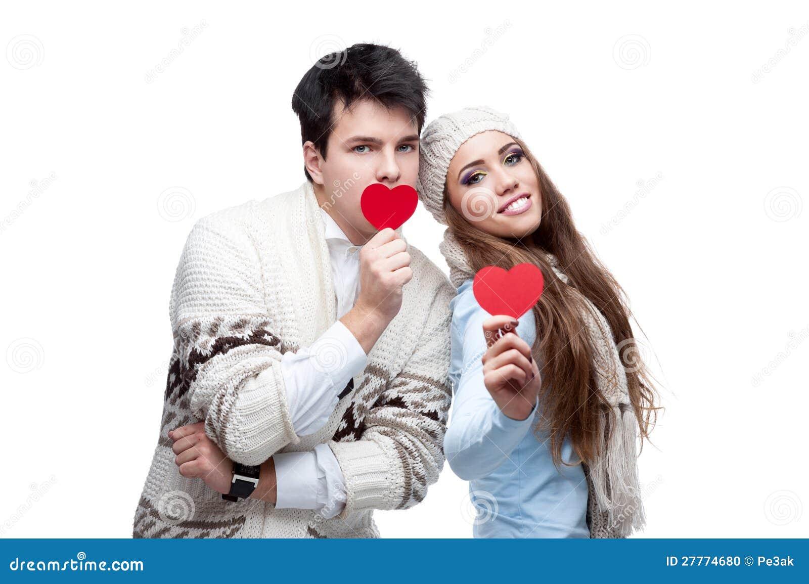 Jeunes couples occasionnels gais retenant les coeurs rouges